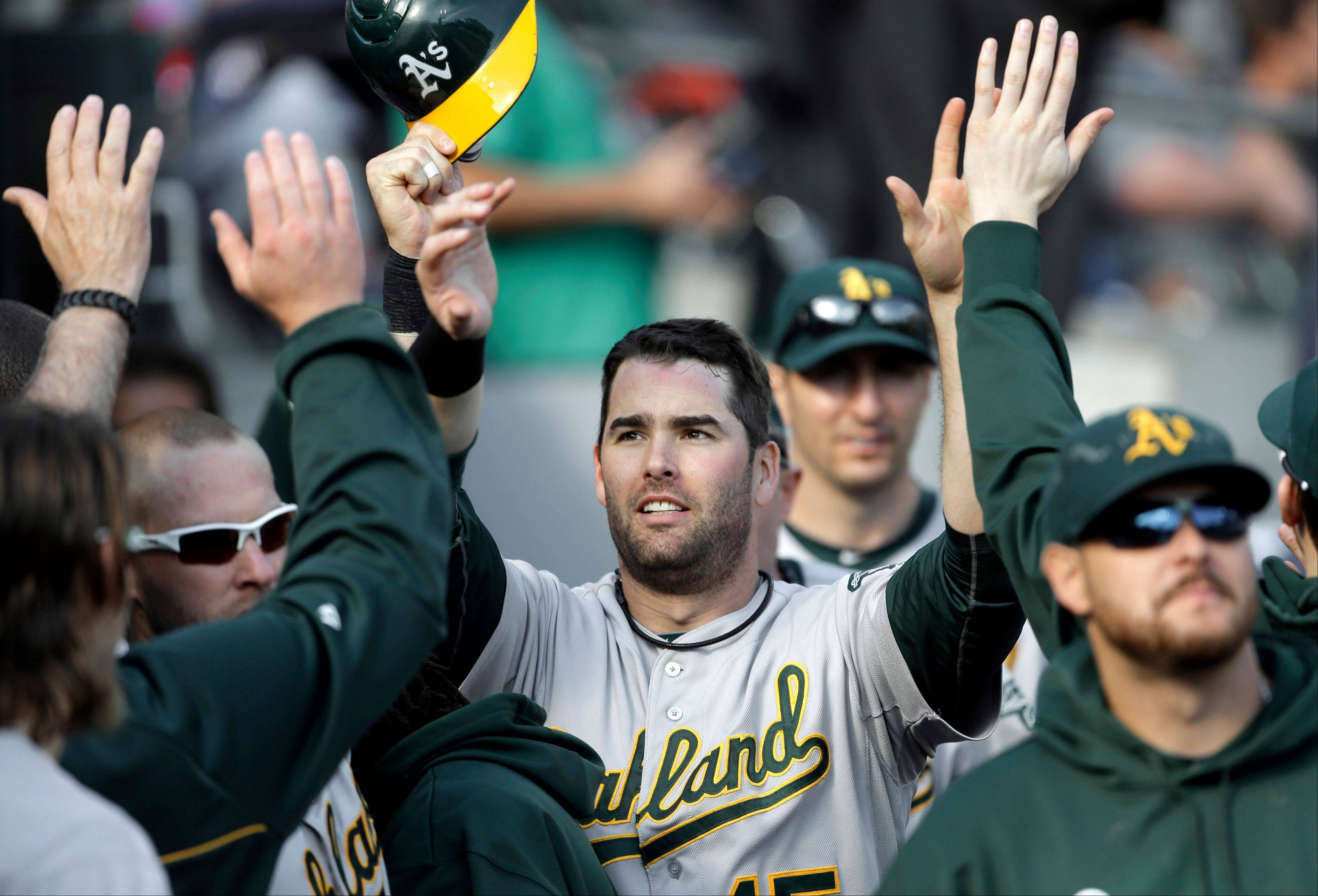 The Oakland Athletics' Seth Smith is congratulated in the dugout Thursday after scoring on an RBI double by Josh Donaldson during the ninth inning against the Detroit Tigers.