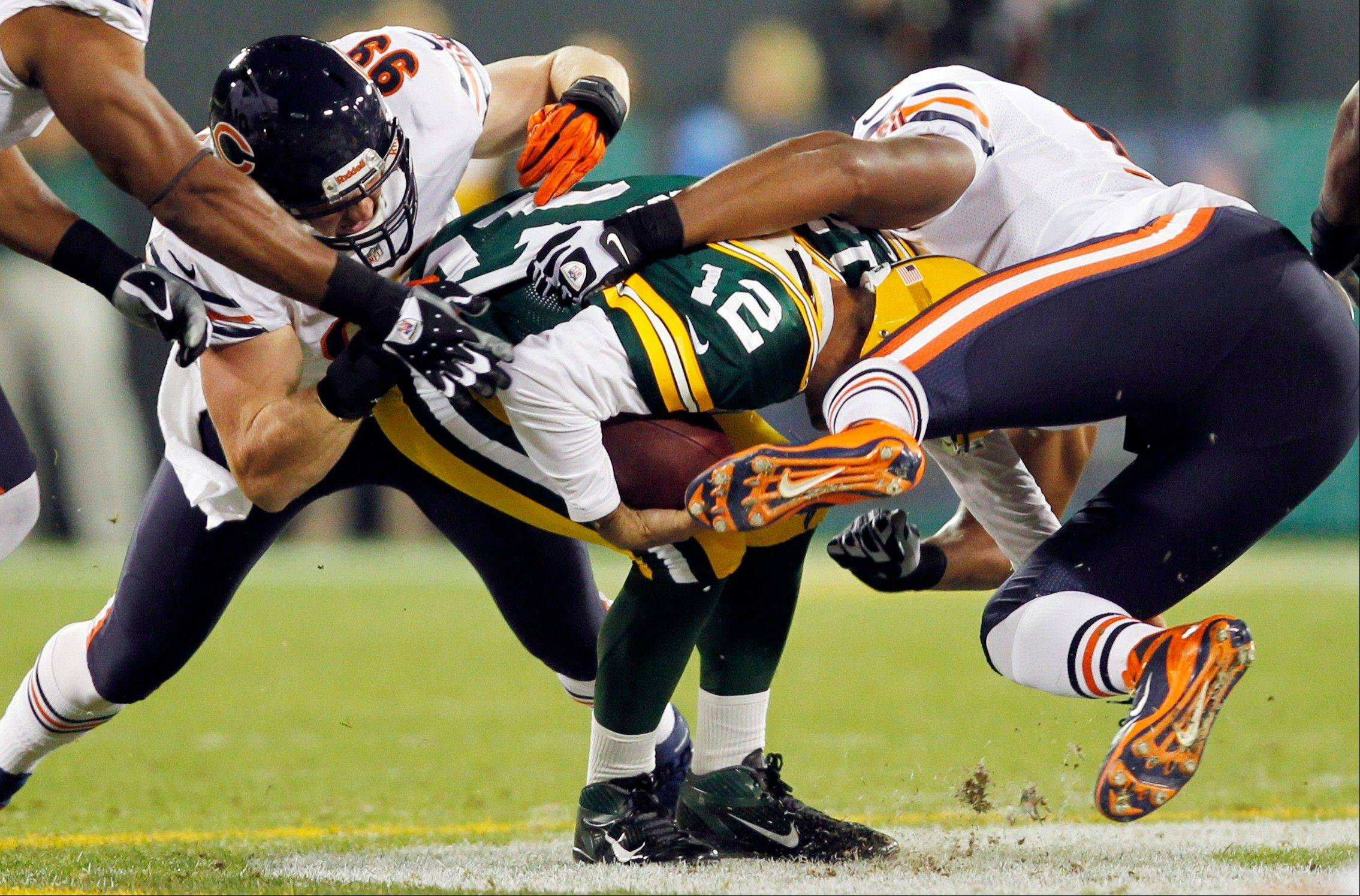 Corey Wootton (98) and Shea McClellin (99) of the Bears combined forces to sack Packers quarterback Aaron Rodgers in their game last week. After two weeks, the Bears' defense already has 8 sacks.