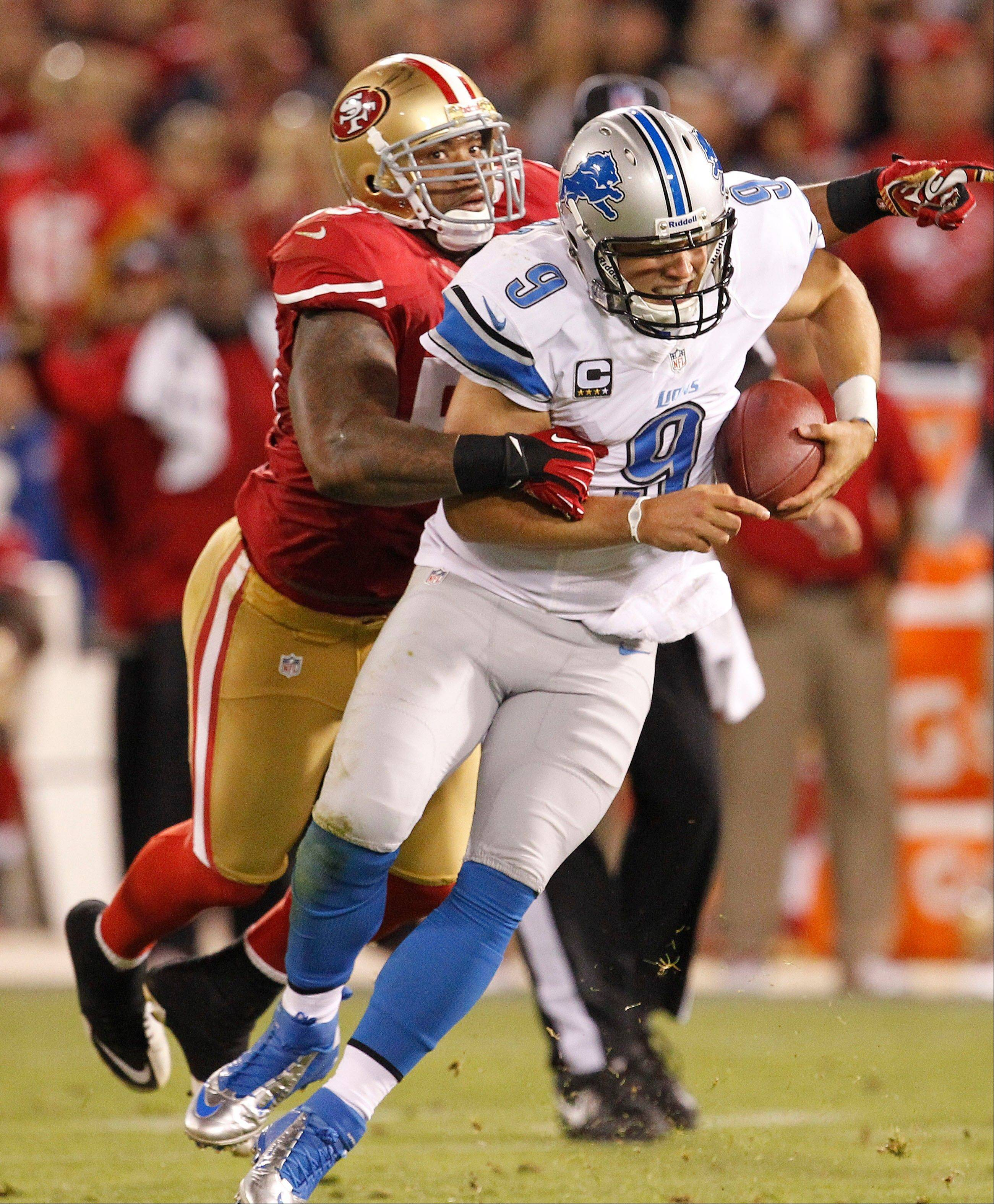 Detroit Lions quarterback Matthew Stafford, right, is brought down by San Francisco 49ers outside linebacker Ahmad Brooks, left, Sunday during the fourth quarter. The 49ers have one of the top defenses in the league and you should think twice about starting running backs when they face them.