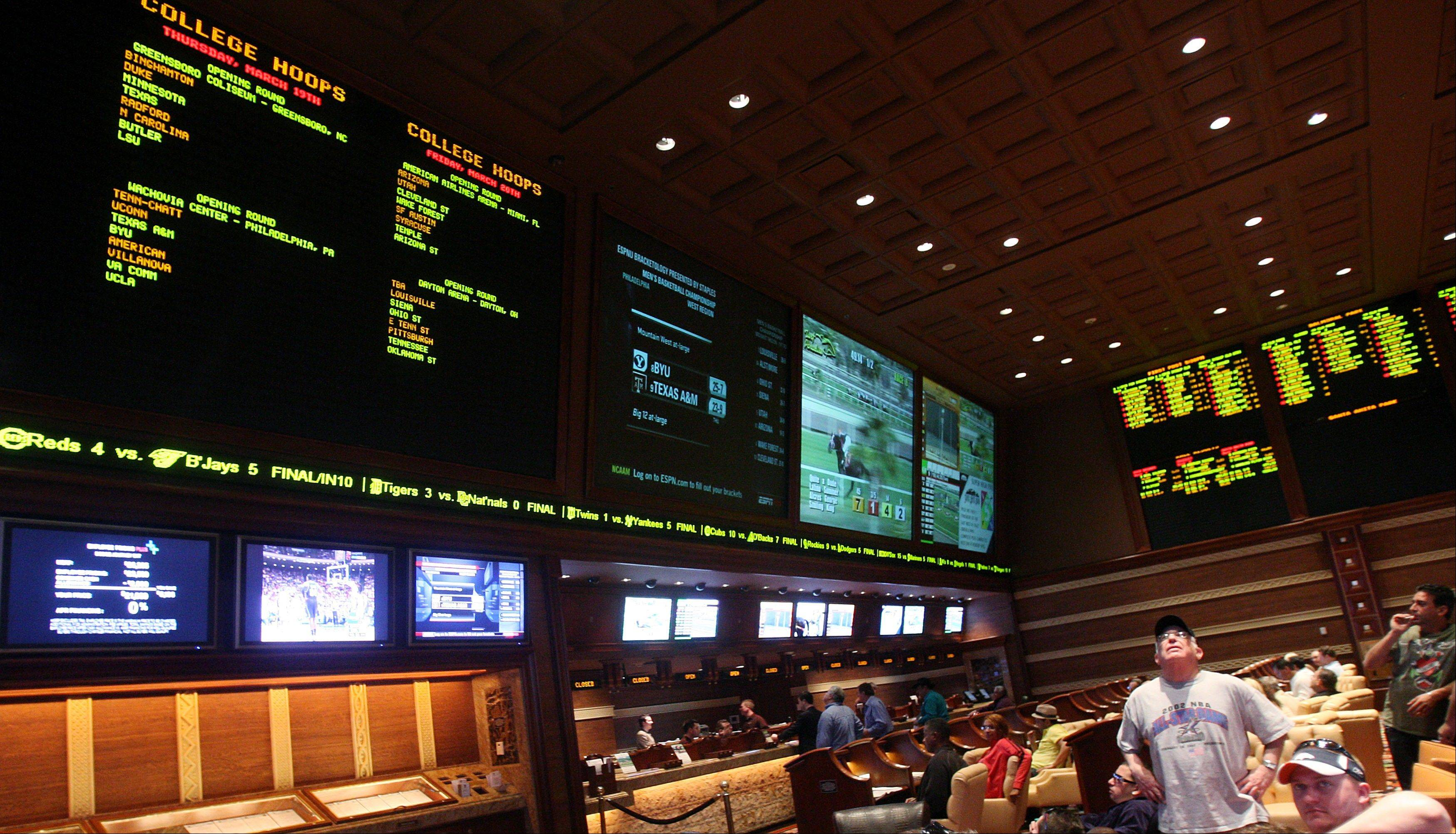 Sports bettors watch the screens in the race and sports book at Wynn Las Vegas, in this March 15, 2009 file photo taken in Las Vegas. Las Vegas casinos think this weekend's NFL week three 2012 games will be the highest-scoring ever -- and that you can thank the league's replacement officials.