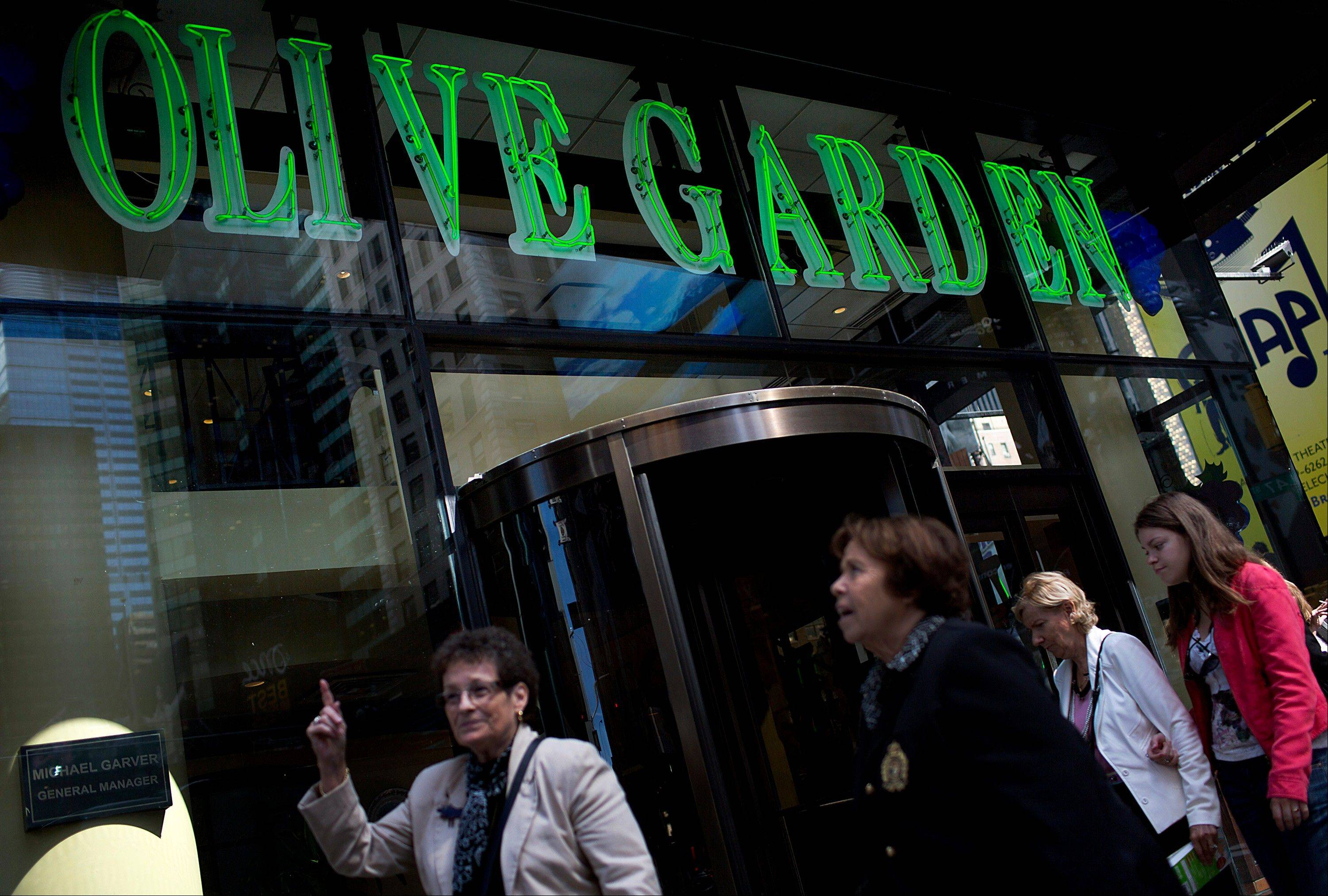 Pedestrians pass in front of an Olive Garden restaurant in New York, U.S., on Wednesday, Sept. 19, 2012. Darden Restaurants Inc., operators of casual dining restaurants in North America, is scheduled to release earnings data on Sept. 21.