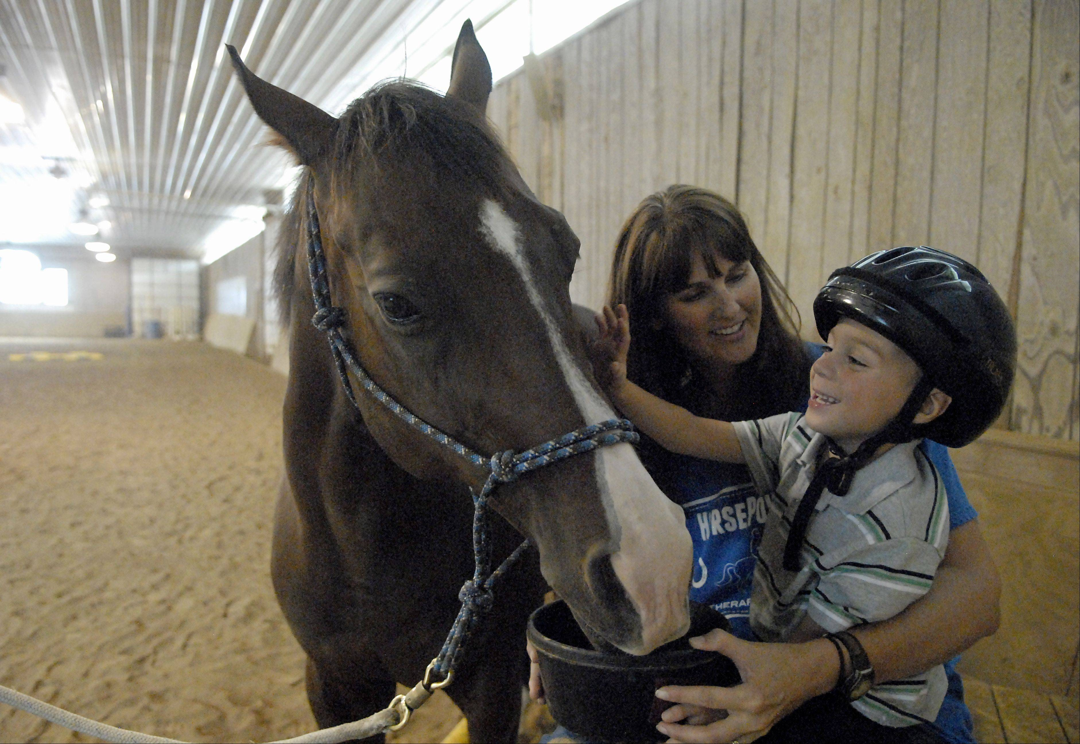 HorsePower Therapeutic Riding director Carrie Capes holds student Trevin Kuhl, 4, of Sycamore, as he feeds a treat to his therapy horse, Ronan.