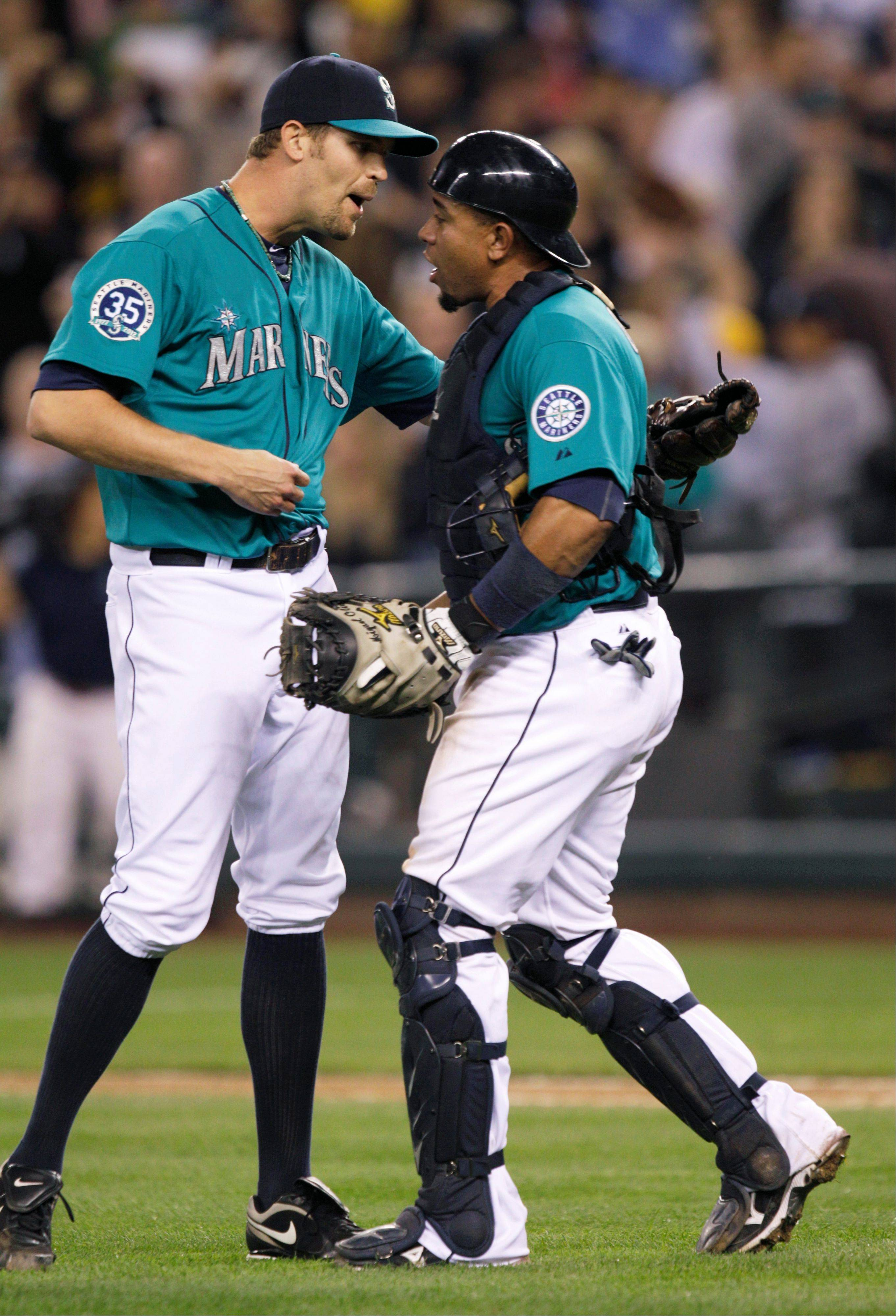 Catcher Miguel Olivo greets closer Tom Wilhelmsen after the Mariners beat the Texas Rangers 6-3 Friday in Seattle. Wilhelmsen earned the save, and Olivo had a two-run home run in the game.