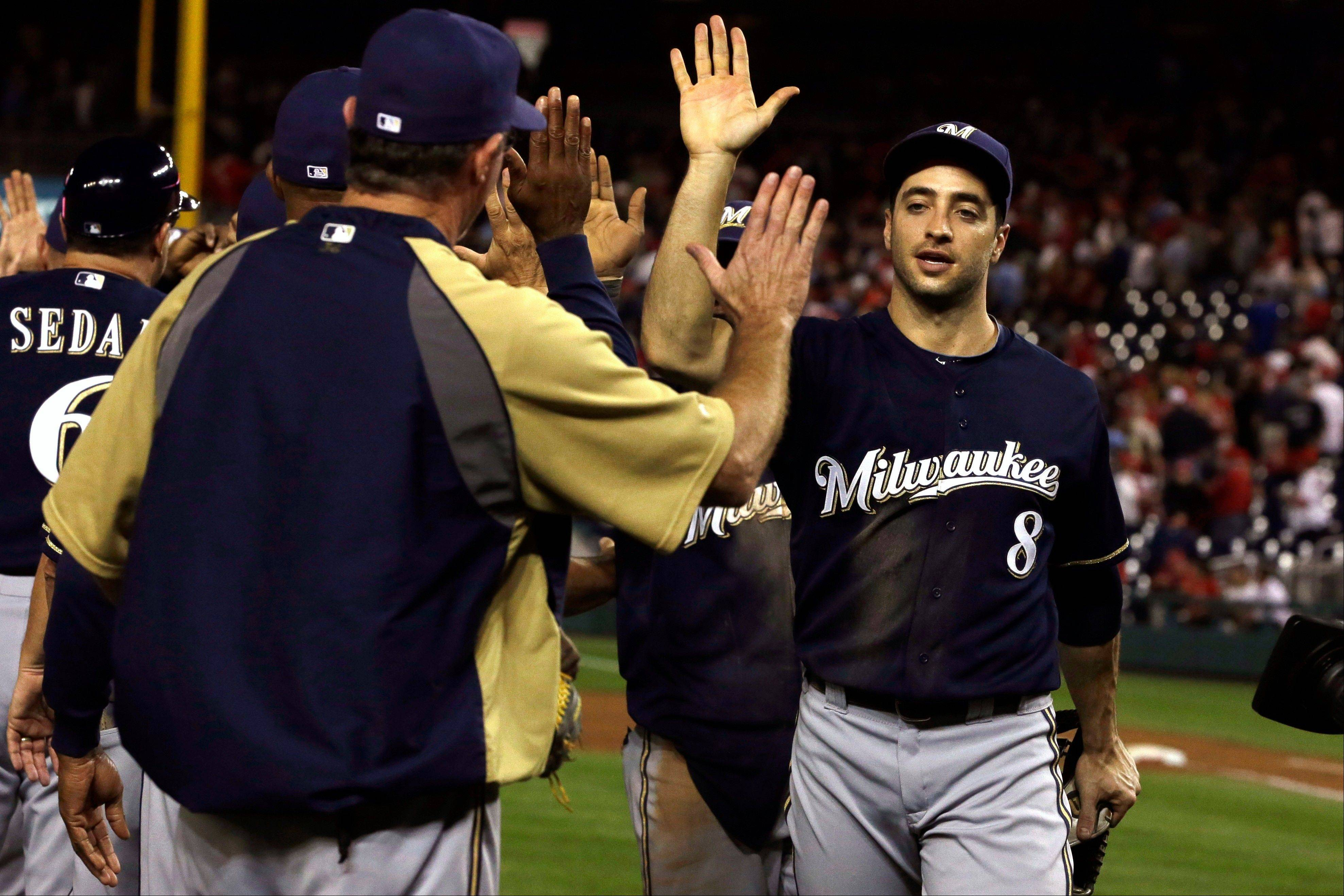 Milwaukee's Ryan Braun (8) high-fives teammates after they downed the Nationals 4-2 on Friday night in Washington.