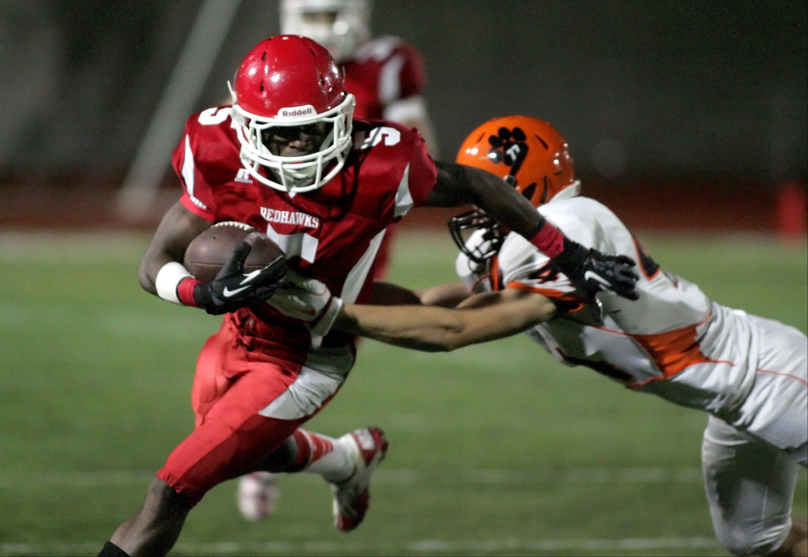 Lasoda Thompson of Naperville Central eludes a tackle.