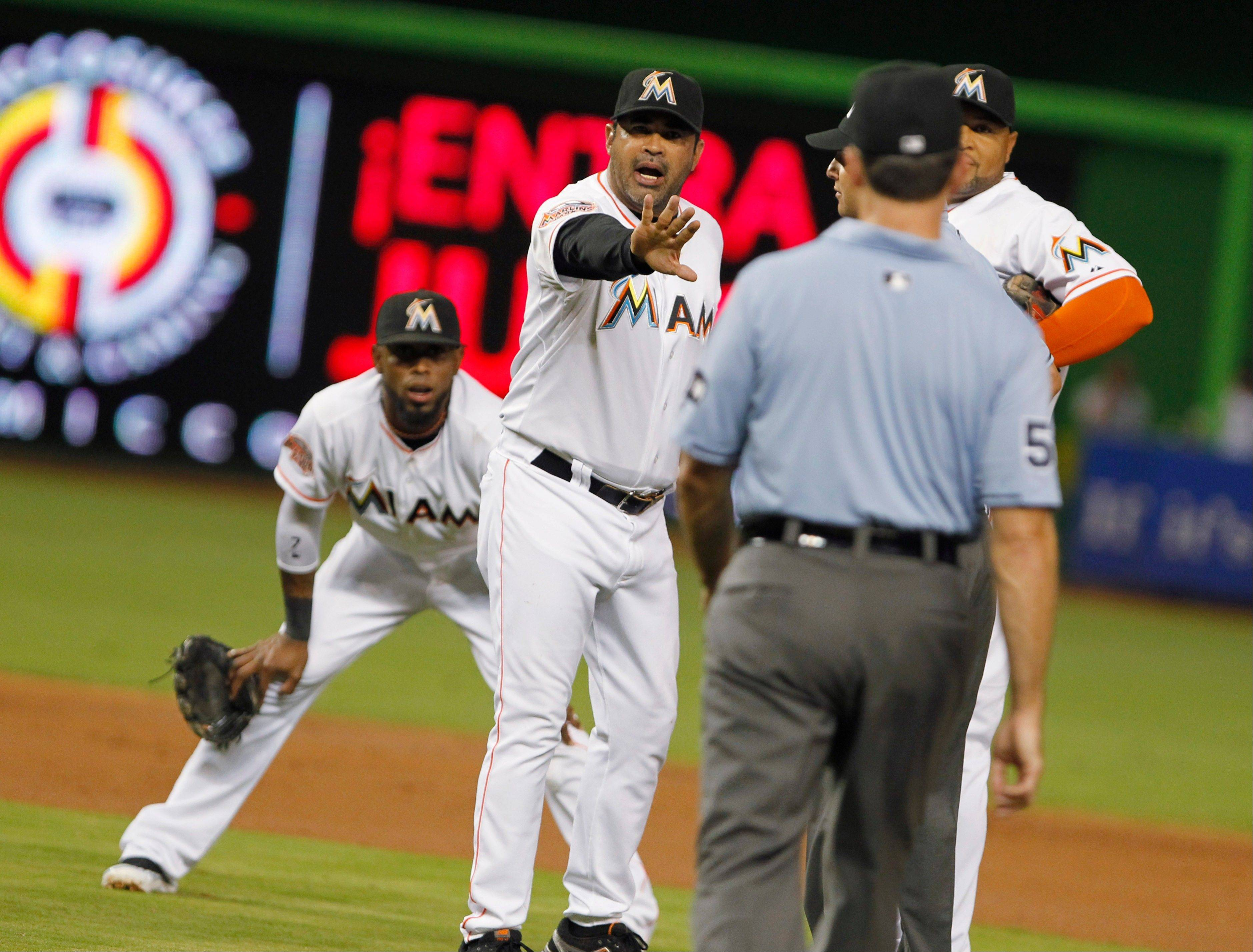 Marlins manager Ozzie Guillen, second from left, argues a call with an official during a game against the Atlanta Braves on Tuesday in Miami. Mindful of speculation his job might be in jeopardy, Guillen says he's glad he rented a house in Miami rather than buying when he took the job.