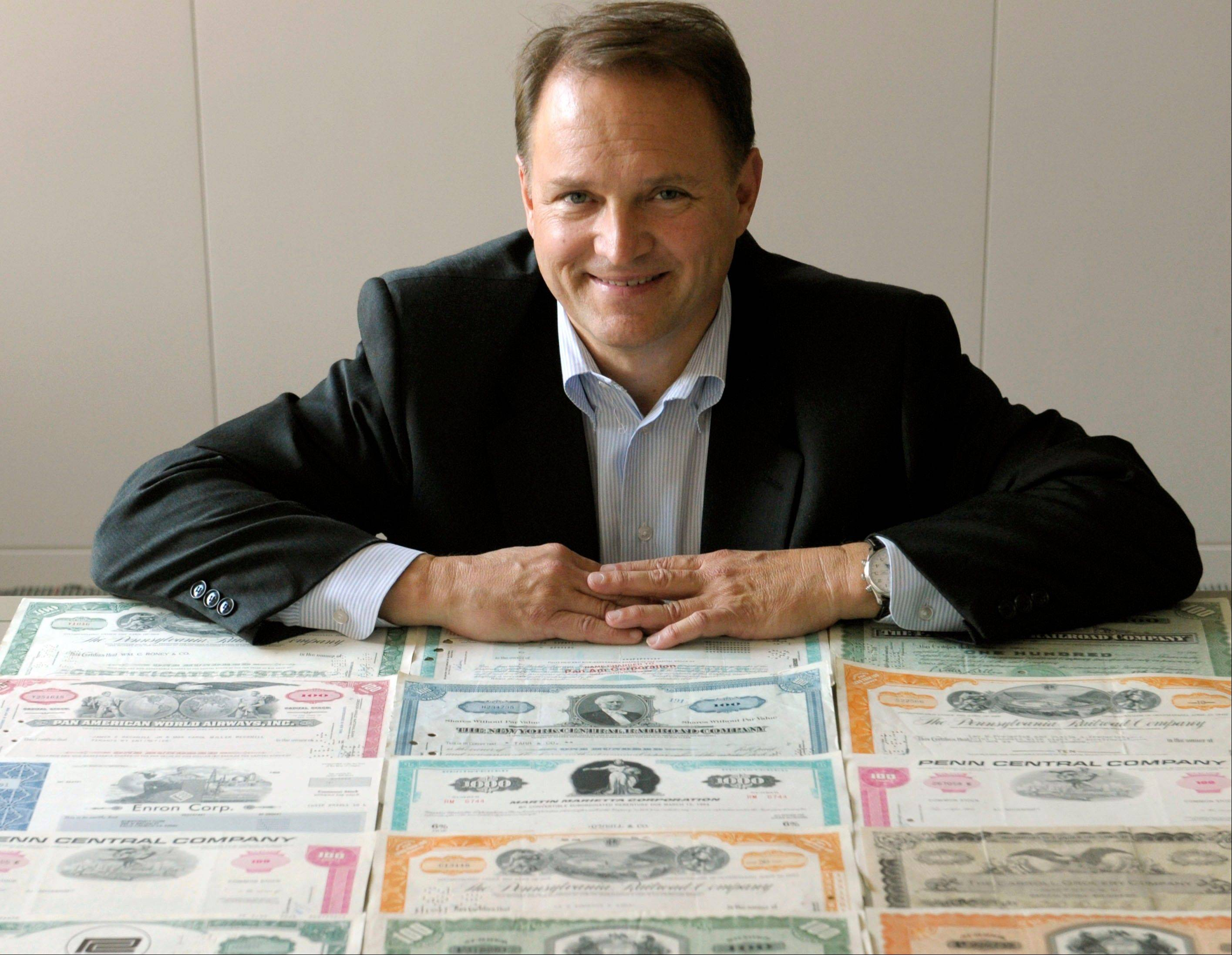 Tom Carroll poses for a portrait with his collection of paper stocks in Washington. At a time when most stock trading is powered by rapid-fire computers, some relish paper stocks for their palpability.