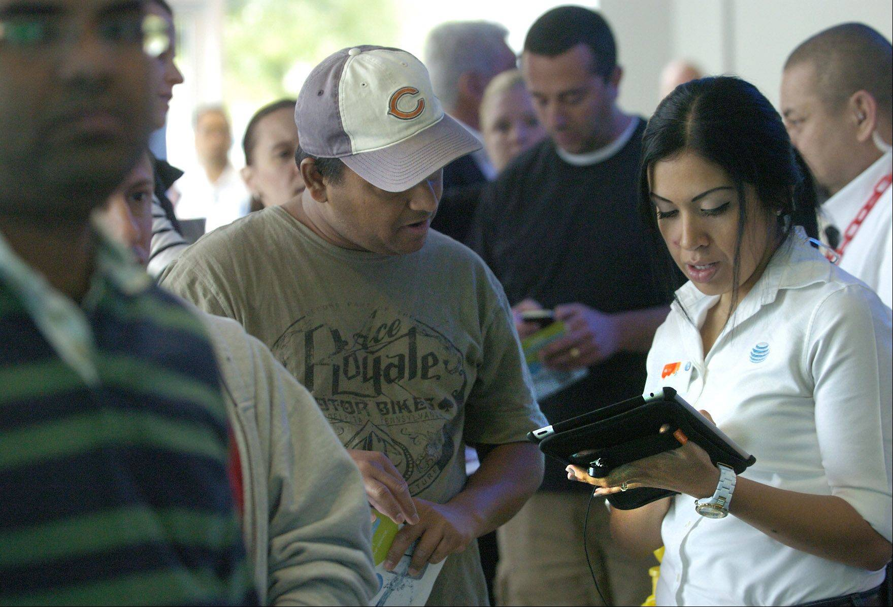 Bob Chwedyk/bchwedyk@dailyherald.comSales support coordinator Juanita Rodriguez sign customers in as they wait in line to purchase the new iPhone 5 at the AT&T Store in Arlington Heights.