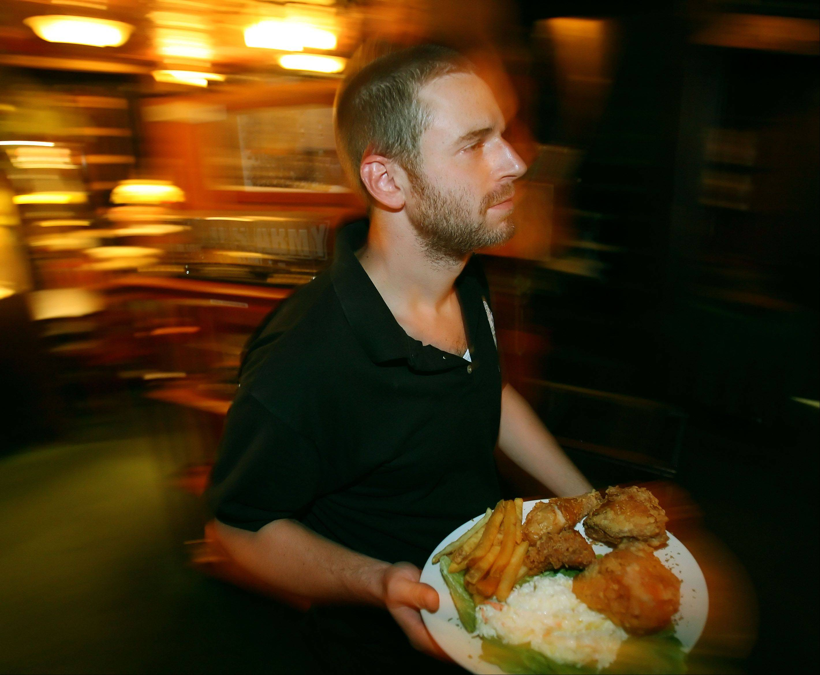 Waiter Mitch Rafalowitz serves up a broasted chicken dinner at The Village Tavern in Long Grove.