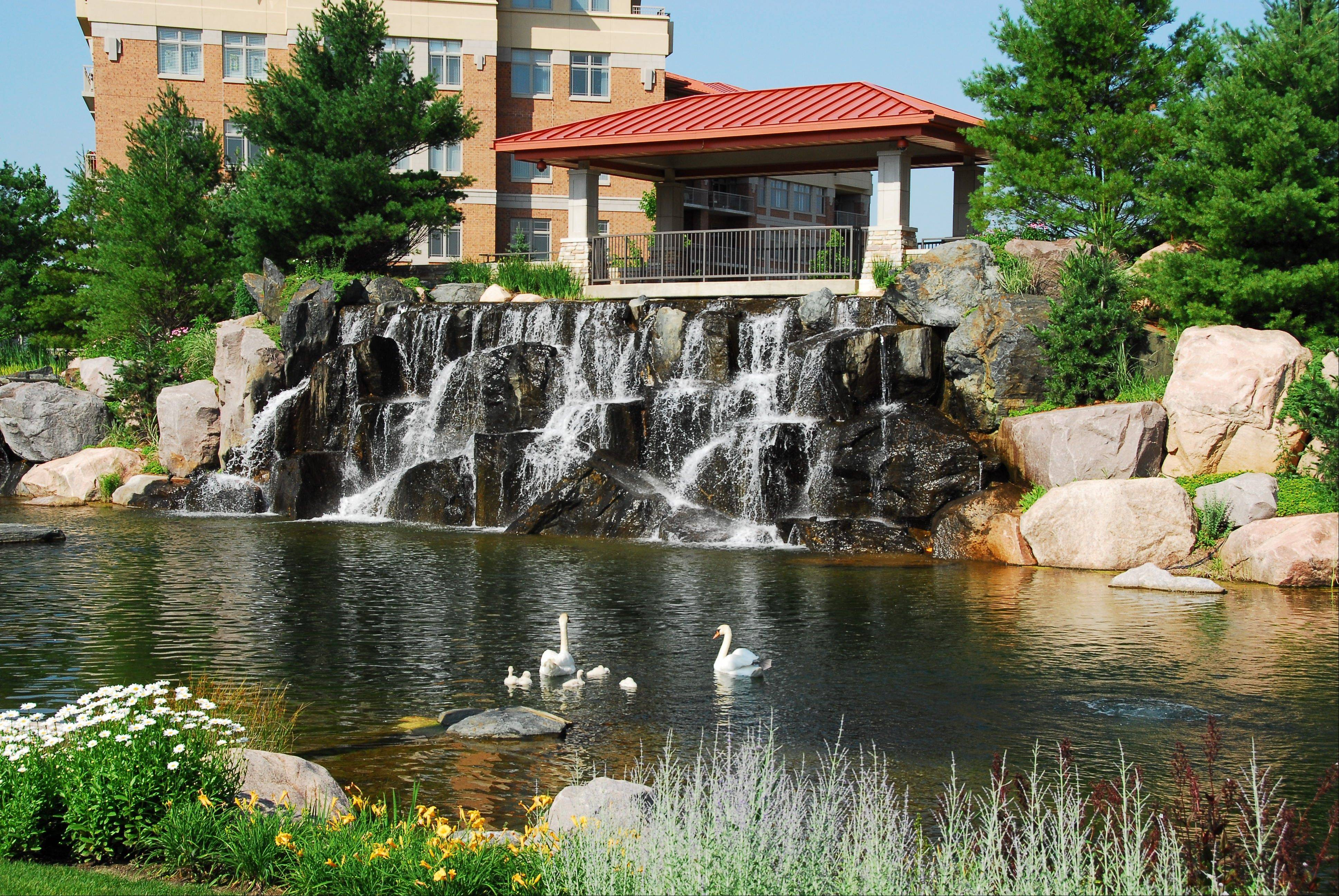 Walking paths, fountains and a waterfall are part of the landscaped grounds at Prairie Park, which features five mid-rise condominium buildings in Wheeling.