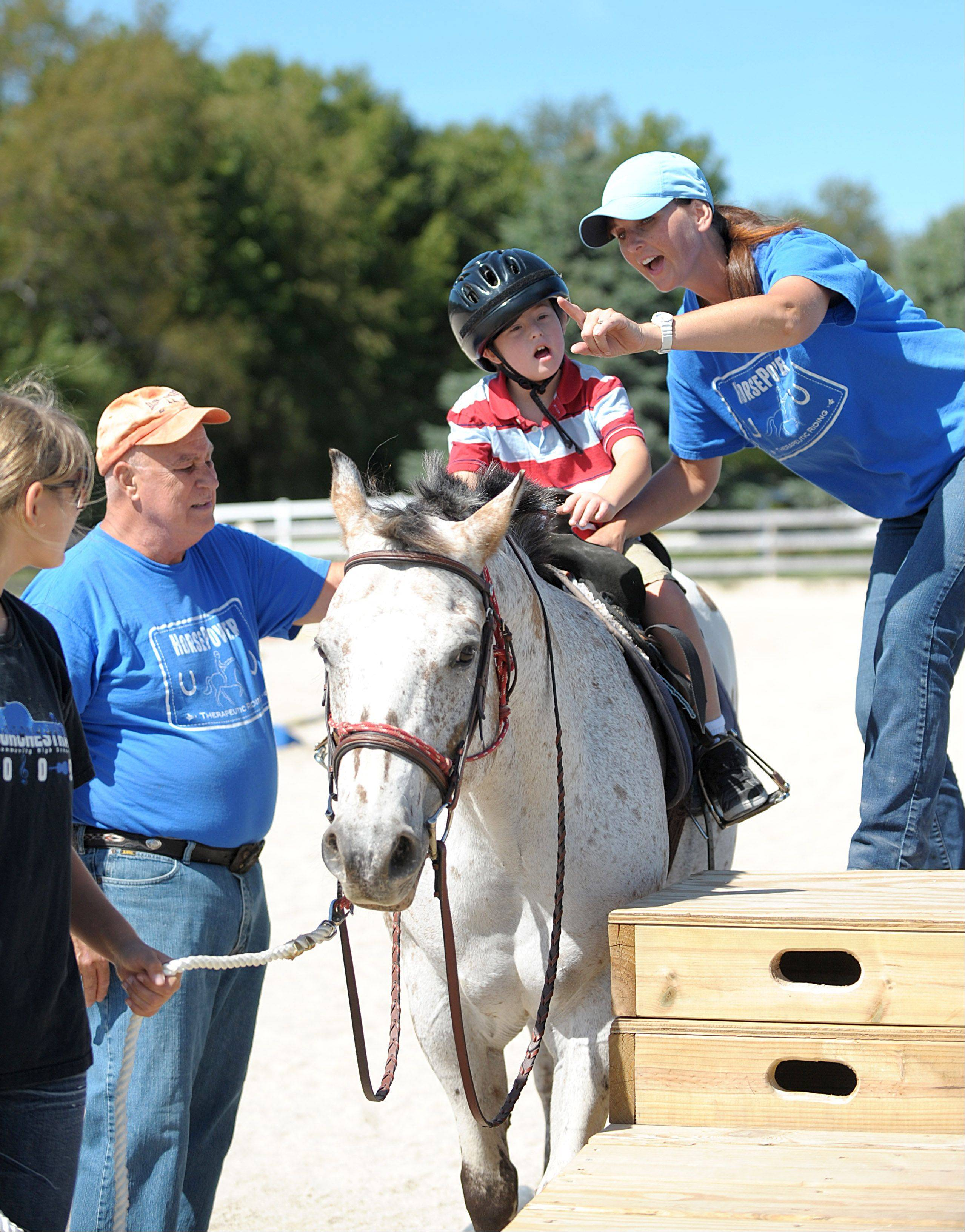 "Carrie Capes encourages David Scott, 8, of DeKalb to say the phrase ""Walk on"" to get his therapy horse, Finale, started for their session at HorsePower Therapeutic Riding in Maple Park. Volunteers Petra Nebergall of Geneva and John Best of Sycamore assist in the session."