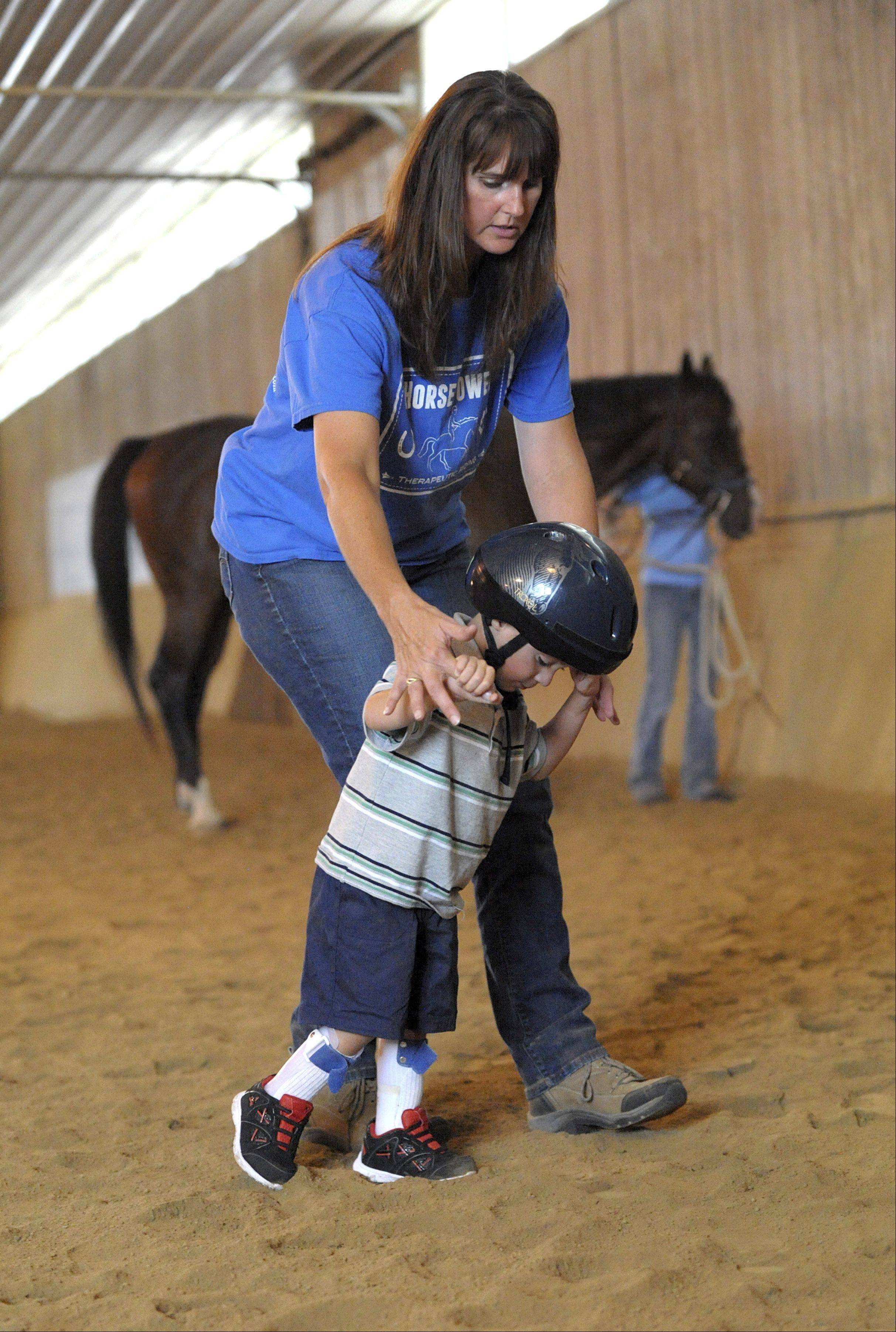 Carrie Capes helps student Trevin Kuhl, 4, of Sycamore walk back to a platform after dismounting his therapy horse, Ronan. The last activity of every session involves the student making a treat for their horse. The program is located at Fox Chase Farms in Maple Park.