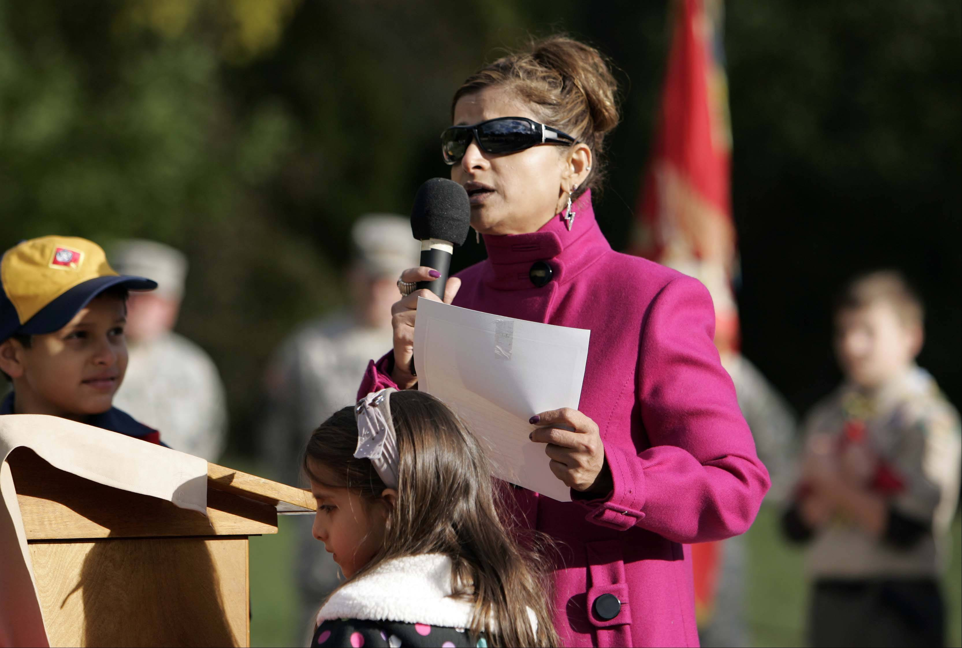 With her children Angeli, 6, and Joshua, 8, at her side, Rashmi Grieco reads a poem about her husband Kevin Grieco, who was killed in Afghanistan in 2008.
