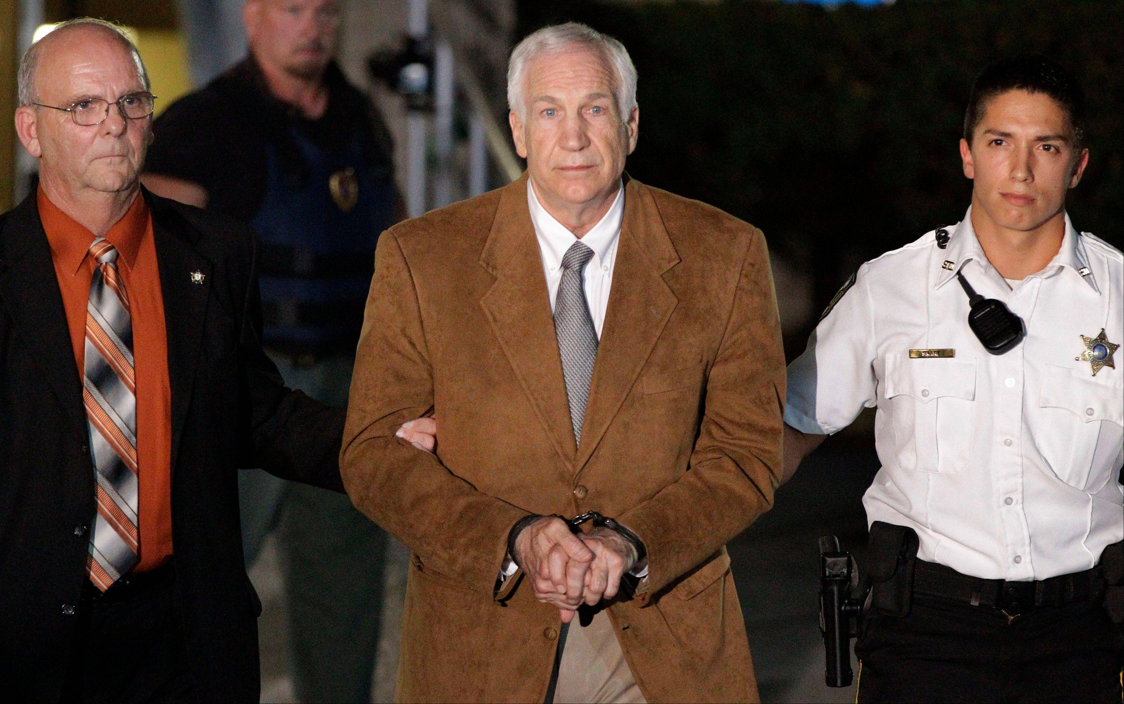 Former Penn State University assistant football coach Jerry Sandusky, center, leaves the Centre County courthouse in custody after being found guilty of multiple charges of child sexual abuse in June in Bellefonte, Pa. He'll be sentenced Oct. 9.