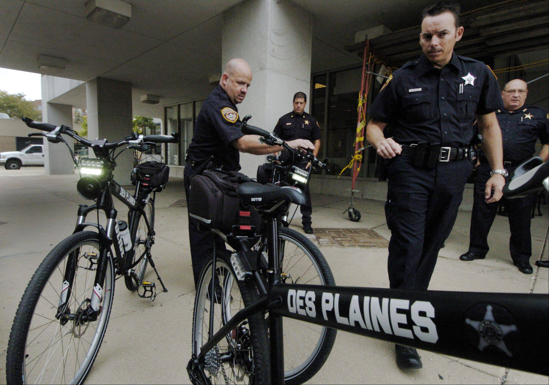 Officers Mike Heidkamp, left, and Trent Beier turn on the flashers as the Des Plaines Police Department displays its new iForce bicycles outside the police station Friday.