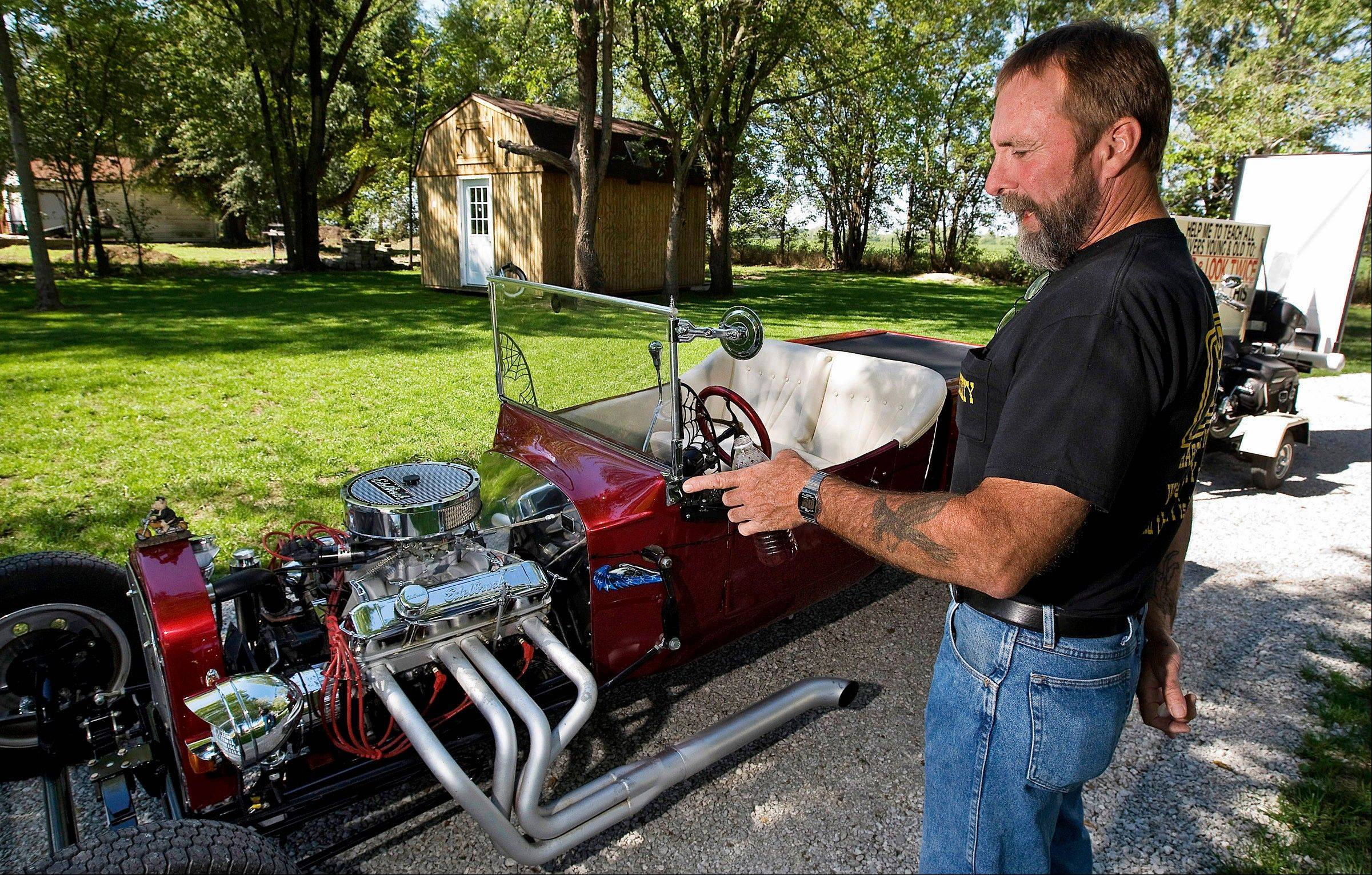 Don Koehler, of Walker, stands next to the 1927 Ford T-bucket he purchased and fixed up after sustaining injuries in a motorcycle accident that would restrict him from driving his Harley-Davidson.