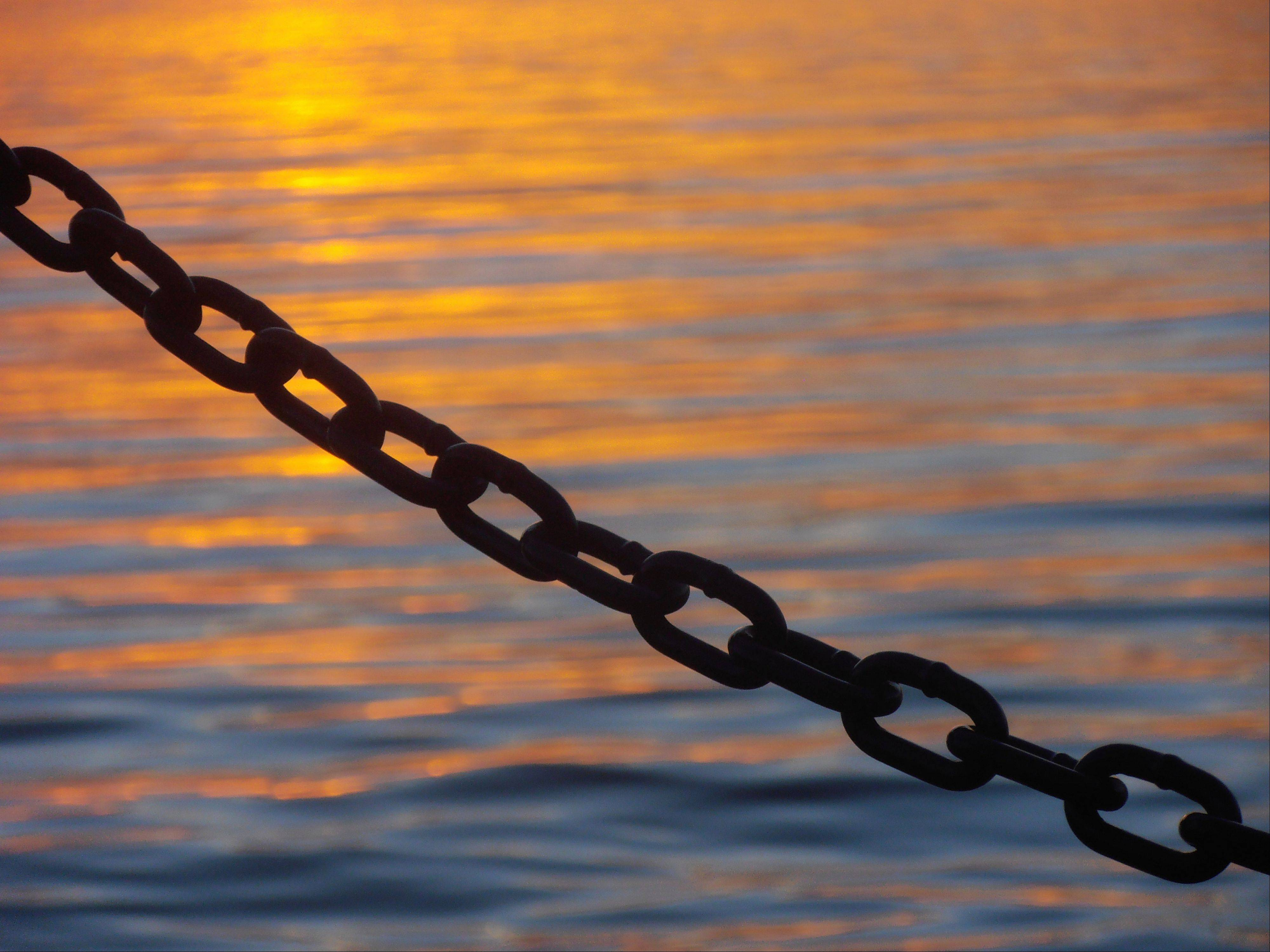 The silhouette of a chain is set off by the sunset reflected on Lake Zurich this summer.