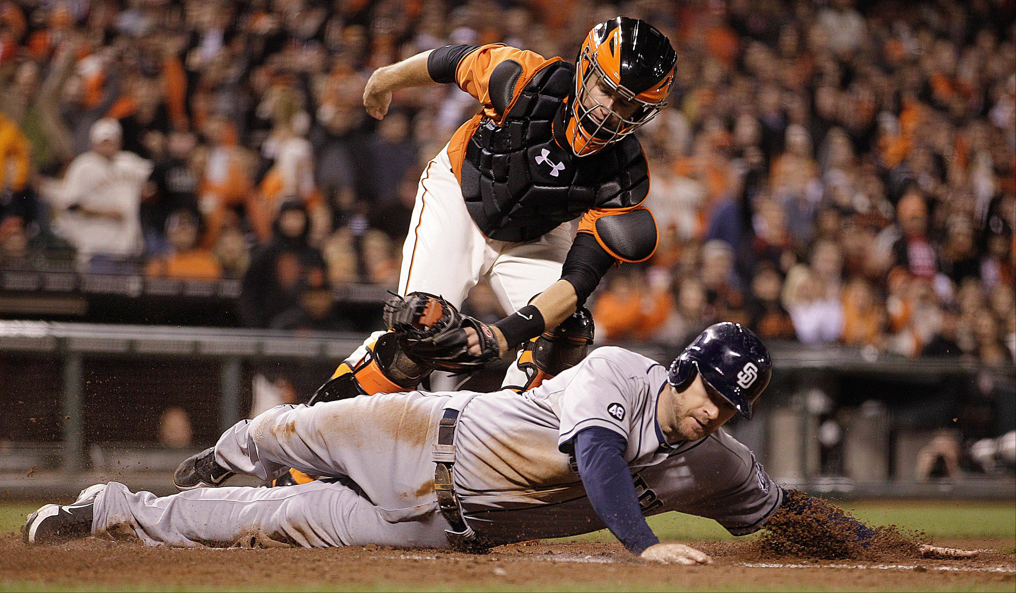 Giants catcher Buster Posey tags out the Padres' Chase Headley at home plate in the sixth inning Friday in San Francisco. Headley attempted to score on a double by Yasmani Grandal.