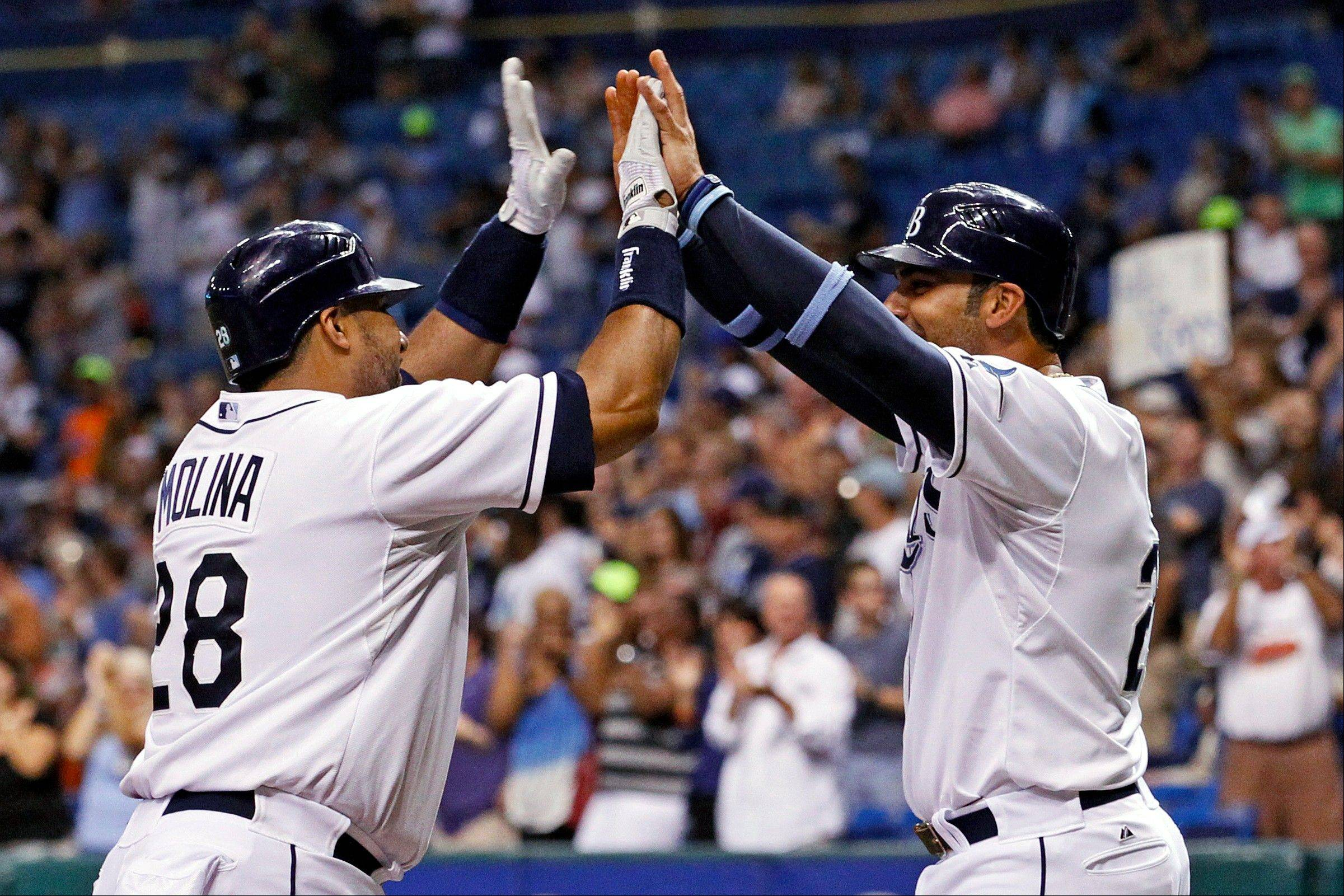 Tampa Bay's Jose Molina, left, is congratulated by teammate Carlos Pena after his two-run home run during the second inning Friday against Toronto in St. Petersburg, Fla.