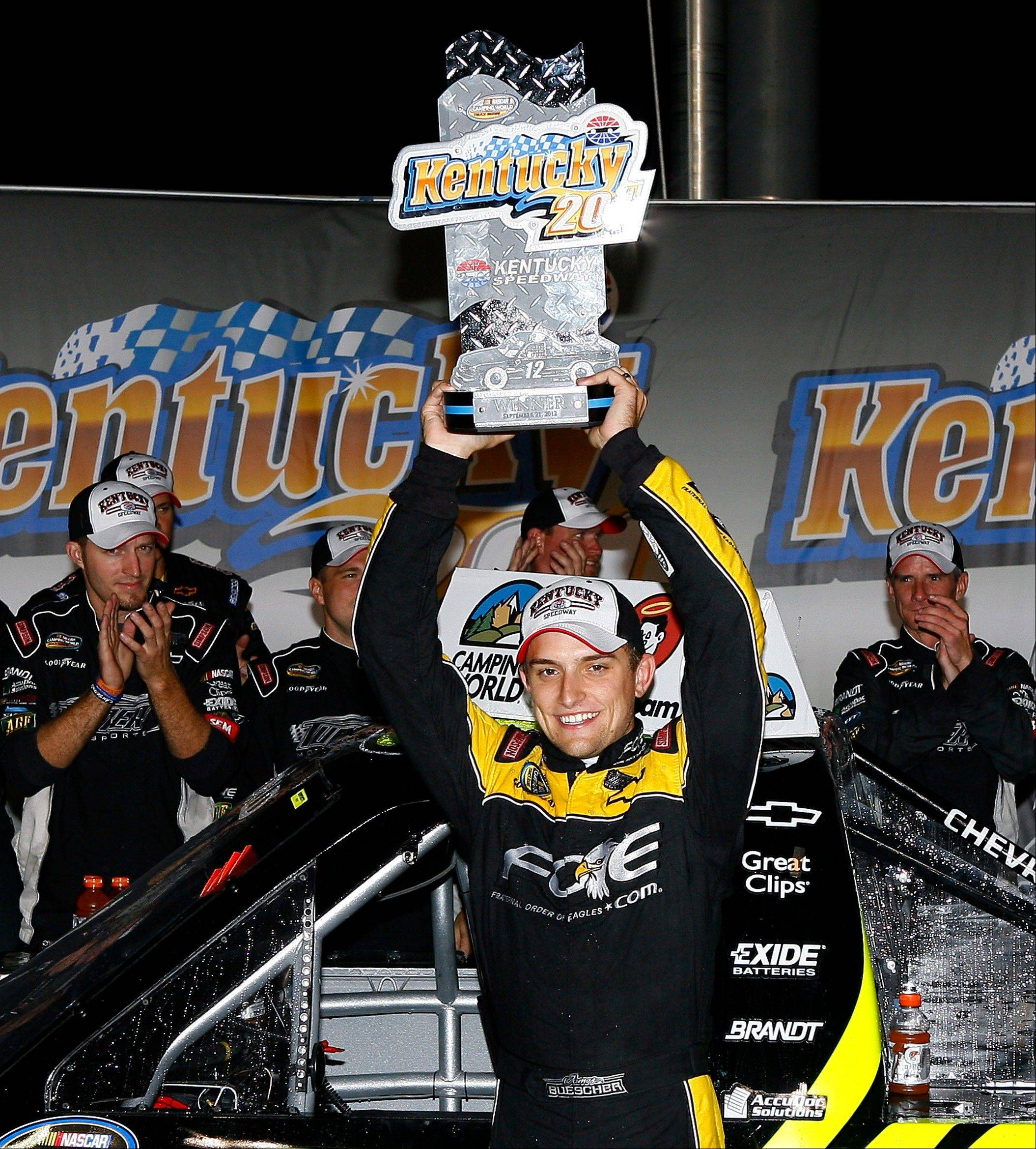 James Buescher hoists the trophy after winning the NASCAR Truck Series auto race at Kentucky Speedway on Friday in Sparta, Ky.