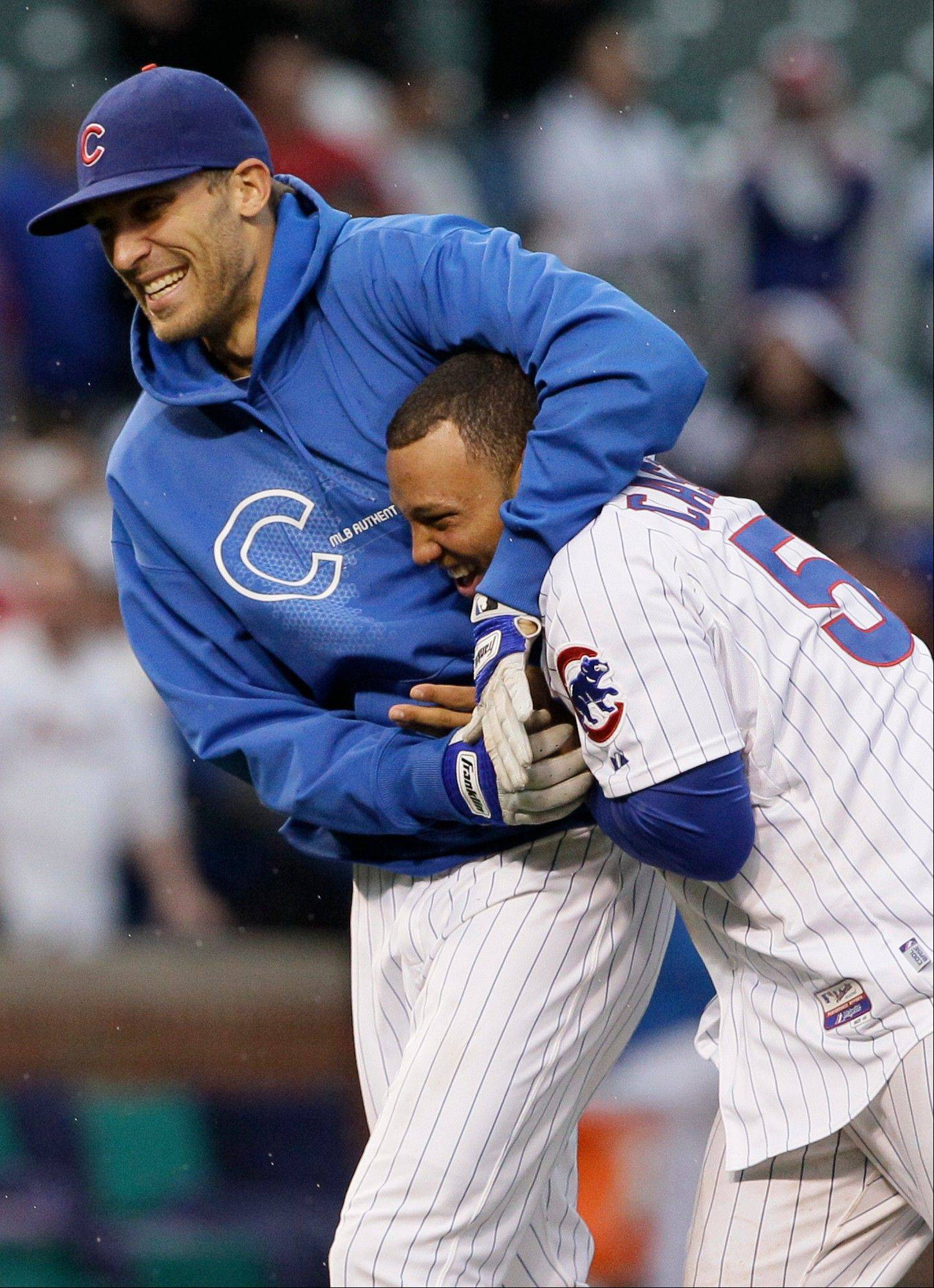 Chicago Cubs' Welington Castillo, right, celebrates with Matt Garza after the Cubs defeated St. Louis Cardinals 5-4 after the 11th inning of a baseball game in Chicago, Friday, Sept. 21, 2012.
