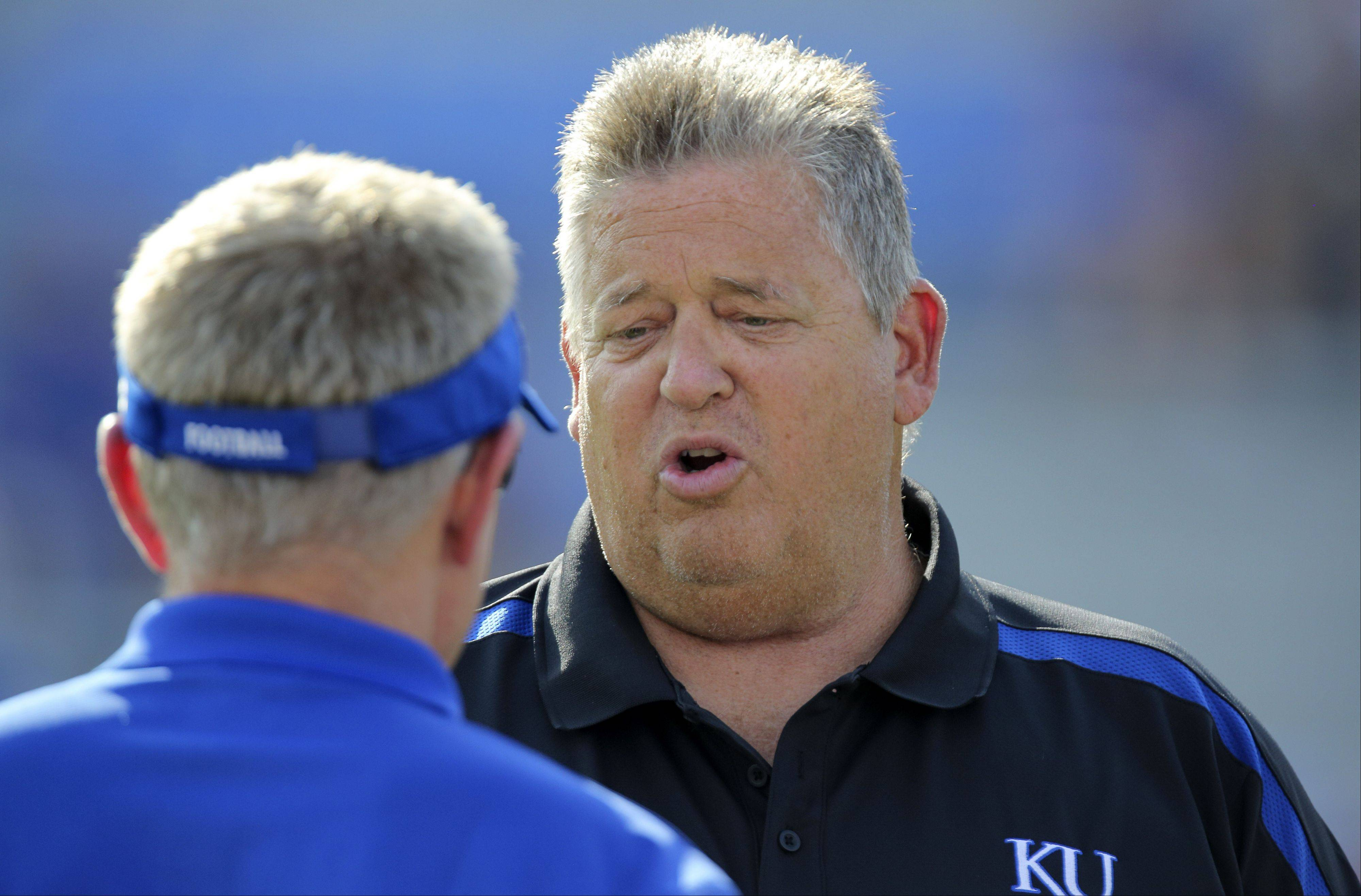 Kansas head coach Charlie Weis, right, will try to end KU's 13-game road losing streak when the Jayhawks take on Northern Illinois in DeKalb. NIU, however, has a 16-game win streak at Huskie Stadium.