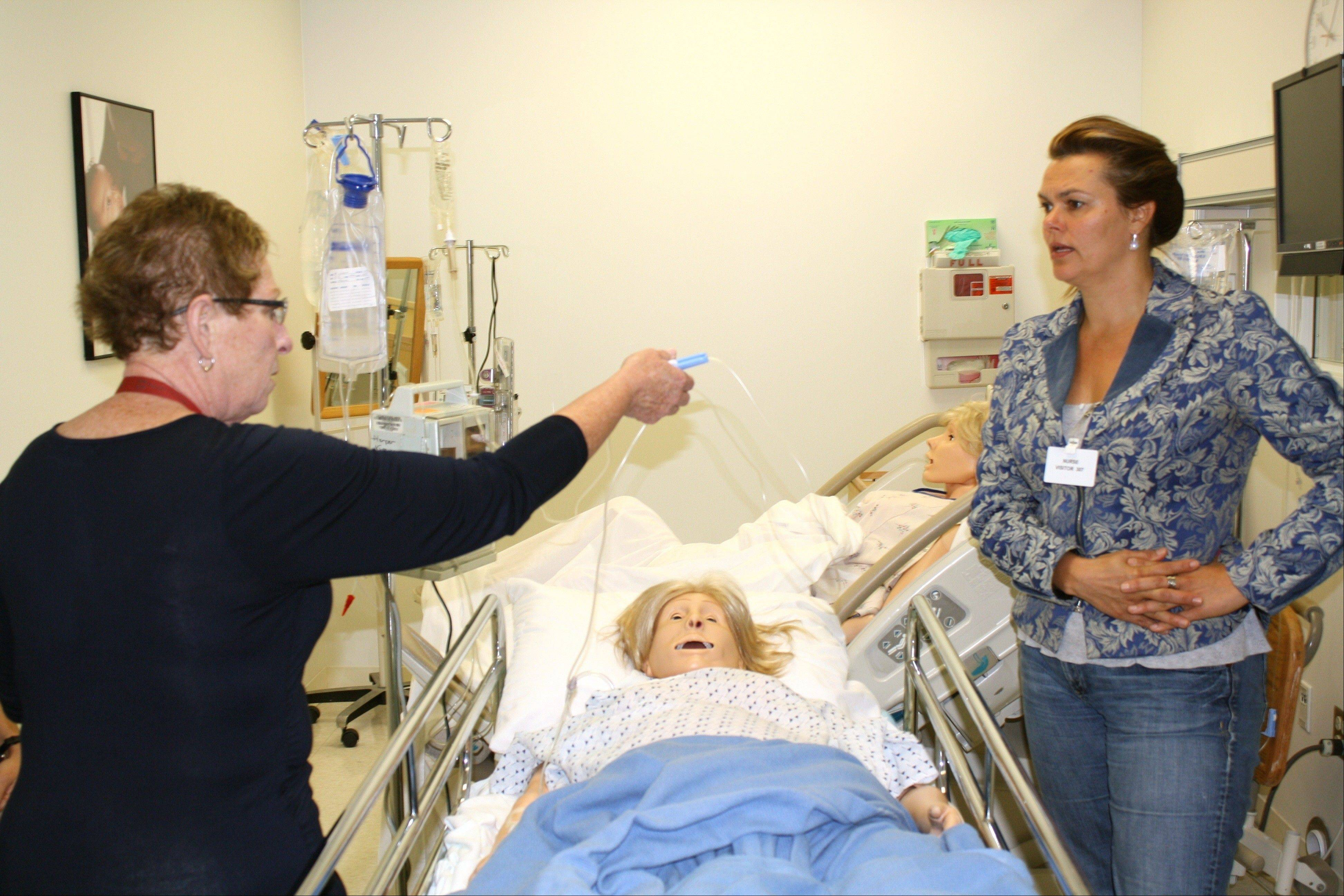 Pat Egel, left, a clinical supervisor at the Simulation Hospital at Harper College, shows Netherlands visitor Linda Kronenberg how new nurses are educated.