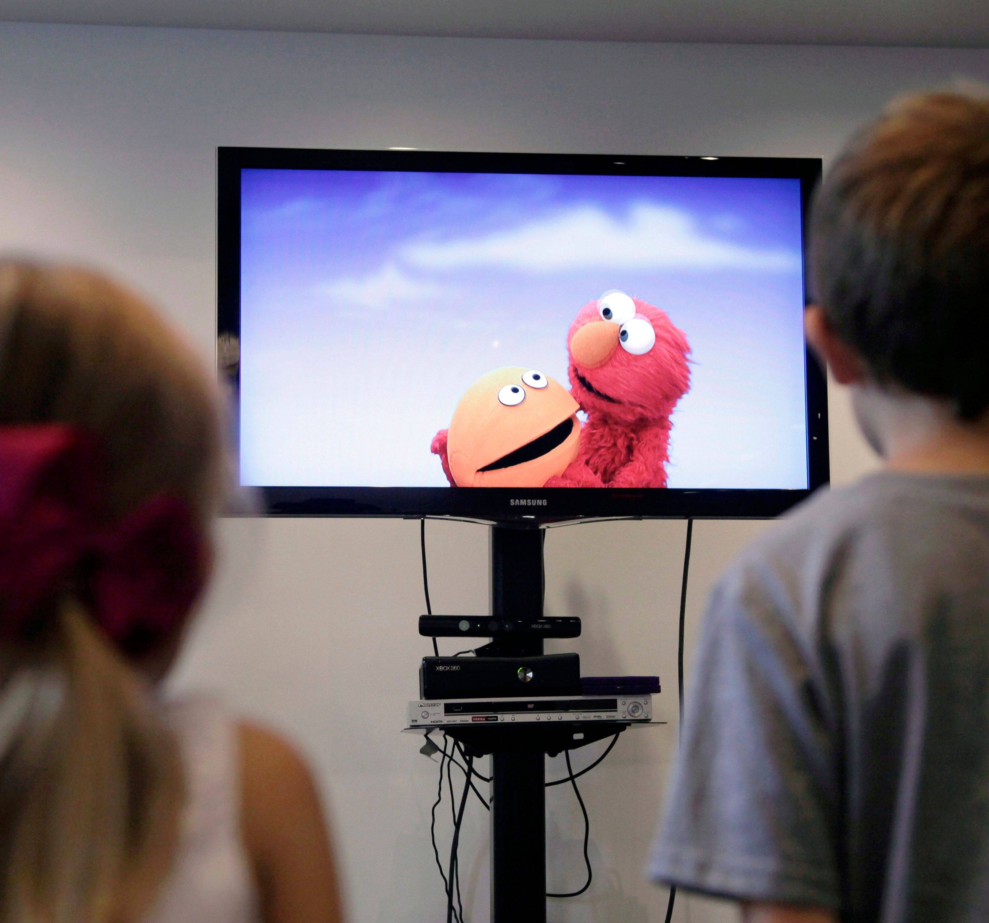 "Zoe Shyba, 3, and Aidan Lain, 7, play ""Kinect Sesame Street TV"" at the Sesame Street Workshop in New York. ""Kinect Sesame Street TV"", launched Tuesday, uses Kinect, a motion and voice-sensing controller created by Microsoft, to give Elmo, Big Bird and the rest of the Sesame Street crew a chance to have a real two-way conversation with their pint-sized audience. The effort represents the next step in the evolution of television, adding an interactive element to what's still largely a passive, lean-back experience."