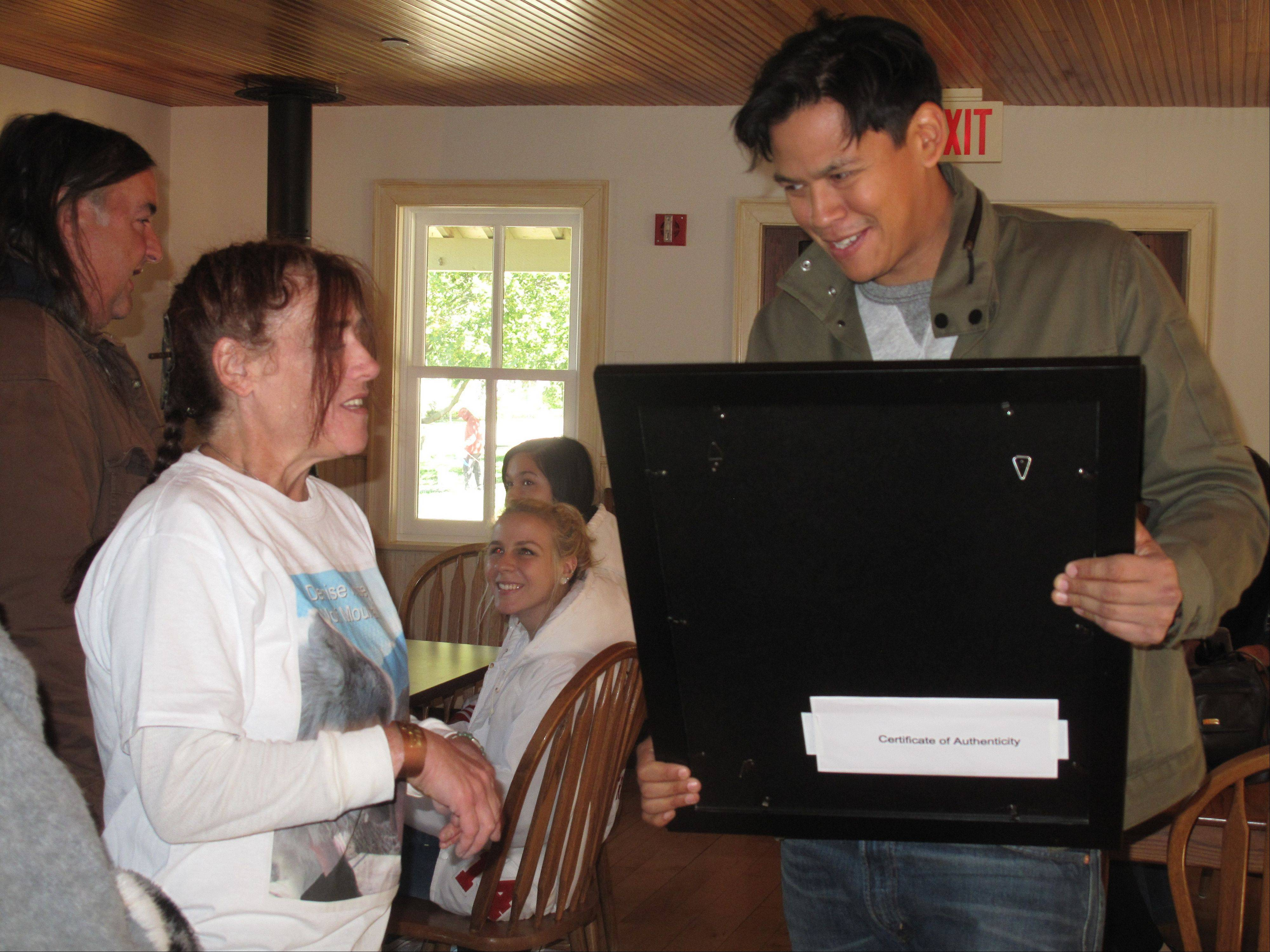 "Denise Kinsey of Naperville presents ""Twilight"" actor Chaske Spencer with a framed photo of the wolf on which his character, Sam Uley, was based. Spencer spoke to fans Saturday at the annual Midwest SOARRING Foundation Harvest Pow Wow at the Naper Settlement."