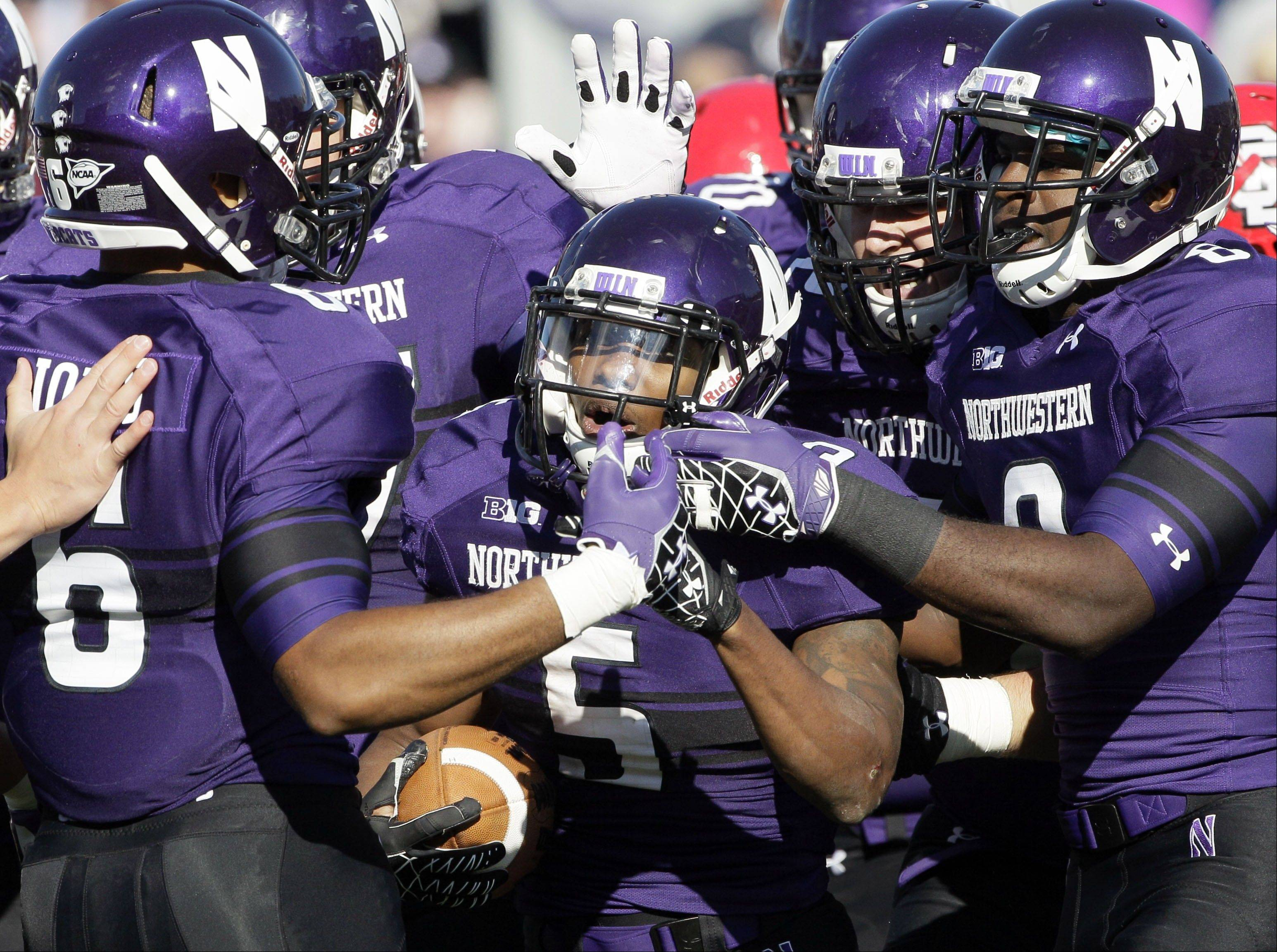 Northwestern running back Venric Mark (5) celebrates a touchdown with teammates Saturday during the first half against South Dakota.