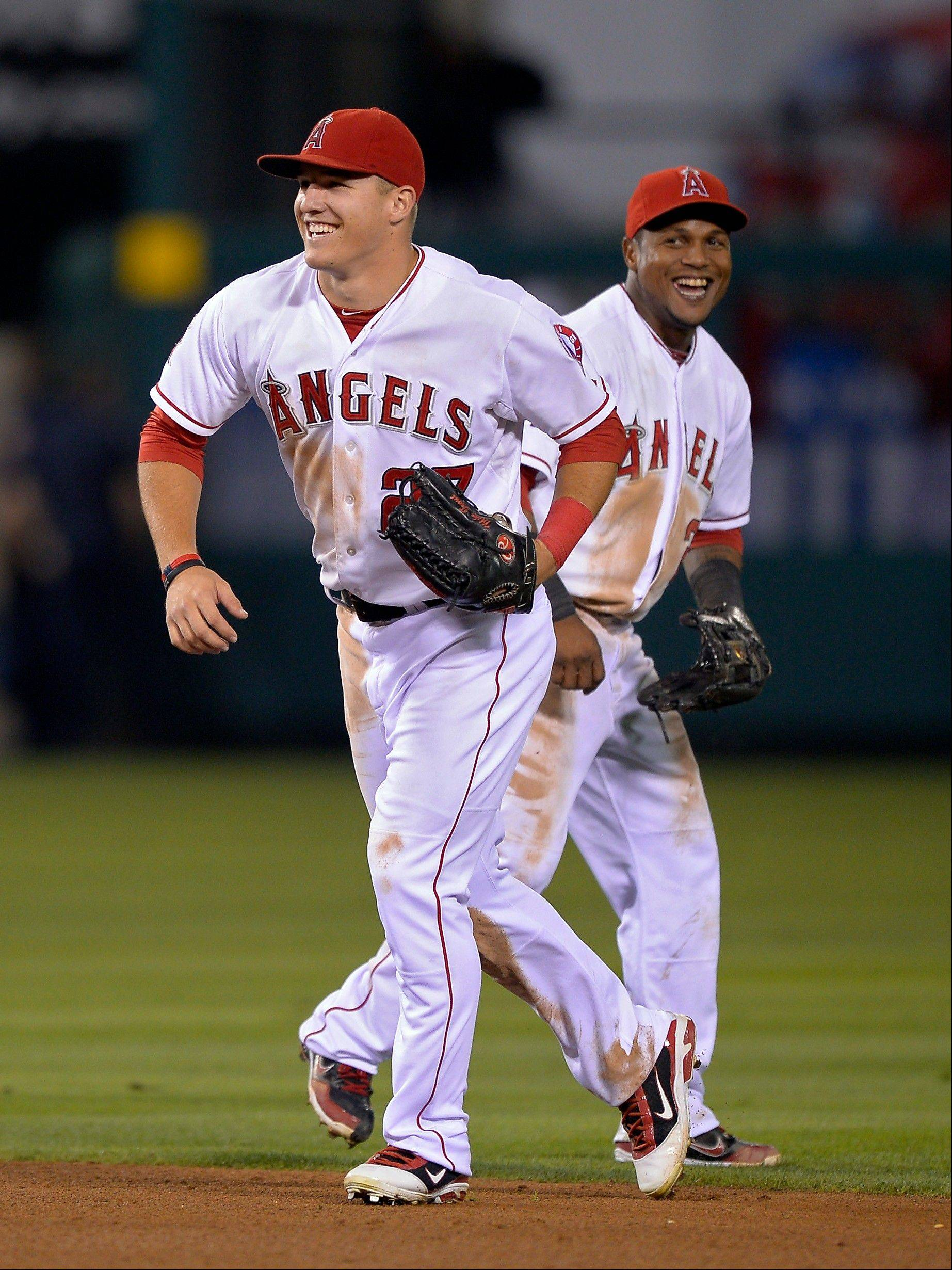 Los Angeles Angels center fielder Mike Trout, left, celebrates with shortstop Erick Aybar after they defeated the Chicago White Sox in their baseball game, Friday, Sept. 21, 2012, in Anaheim, Calif. AP Photo/Mark J. Terrill)