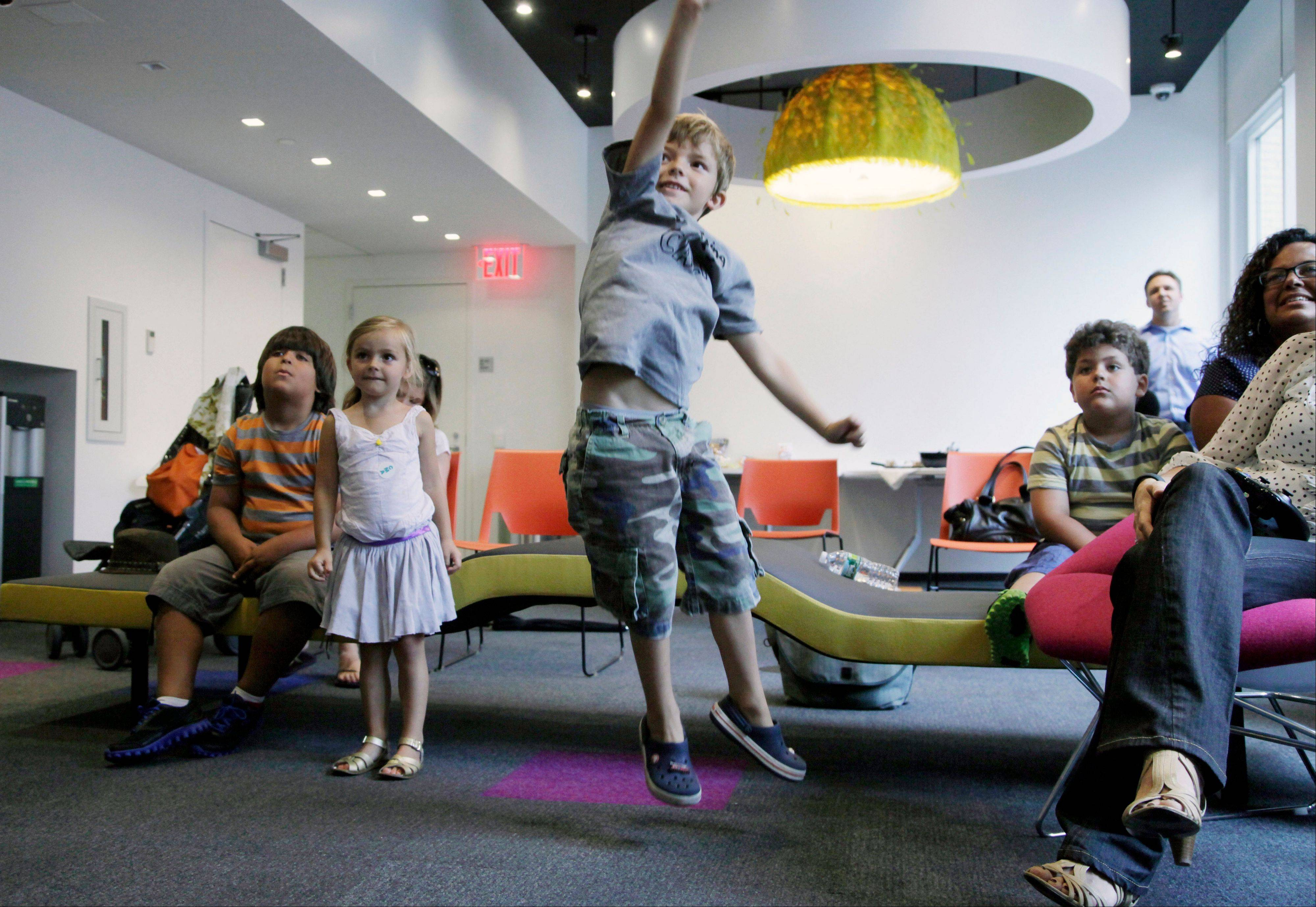 "Aidan Lain, 7, jumps while watching ""Kinect Sesame Street TV"" at the Sesame Street Workshop in New York."