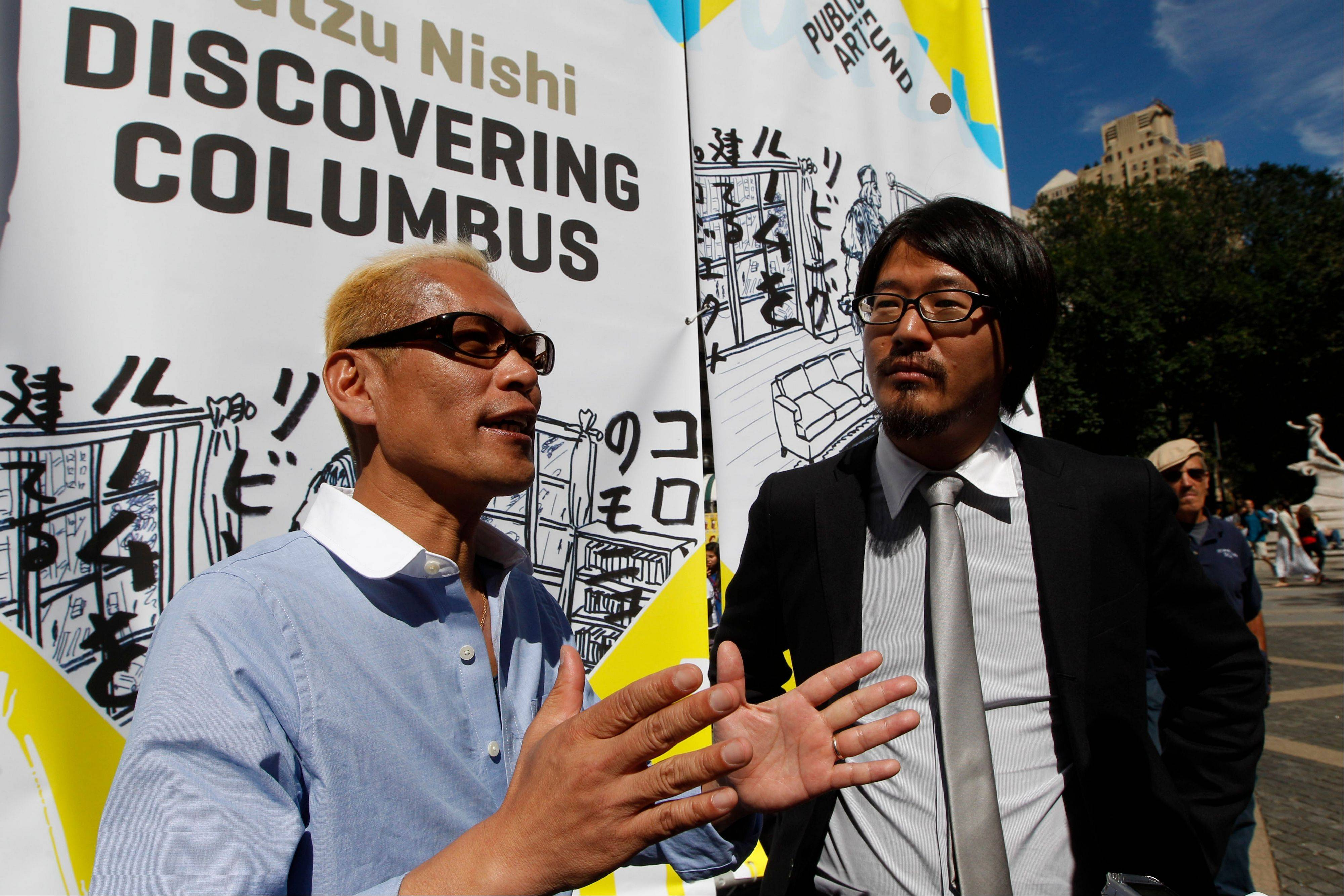 "Japanese artist Tatzu Nishi, left, speaks to reporters with the help of translator Kasuke Fujitaka during a media preview of ""Discovering Columbus."""