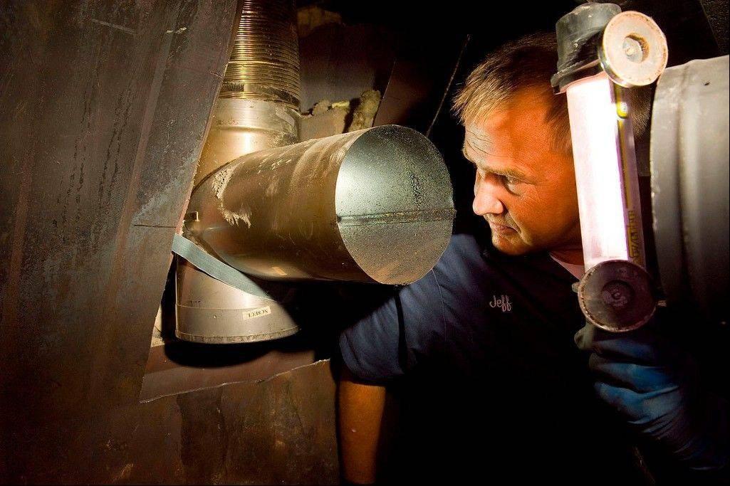 Jeffery Peterson of Potomac Services performs a visual inspection of a chimney flue in Sterling, Va.