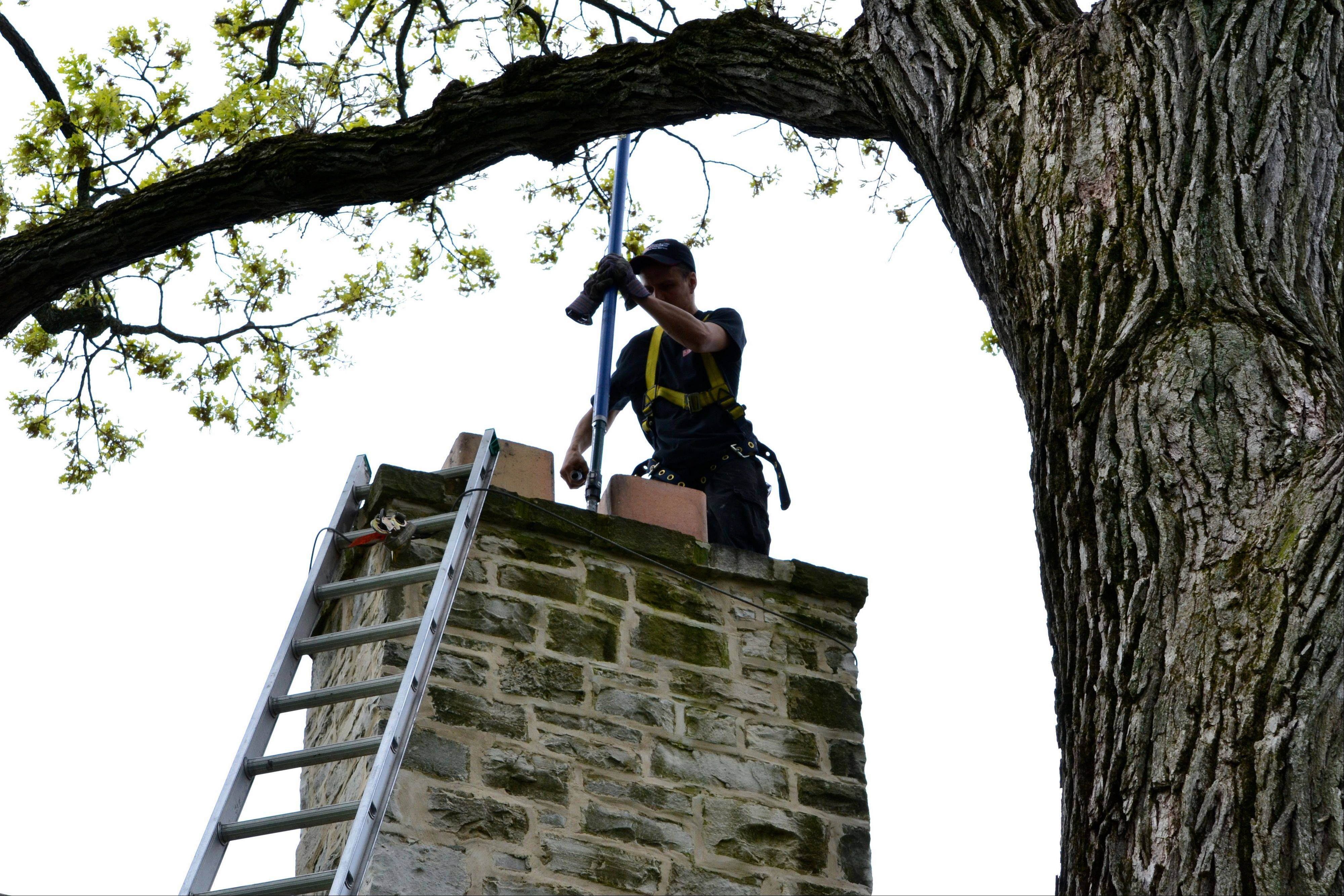 Jacques Leccia of Lindemann Chimney in Lake Bluff cleans the chimney of suburban home this past spring. Leccia is a Chimney Safety Institute of America certified chimney sweep.