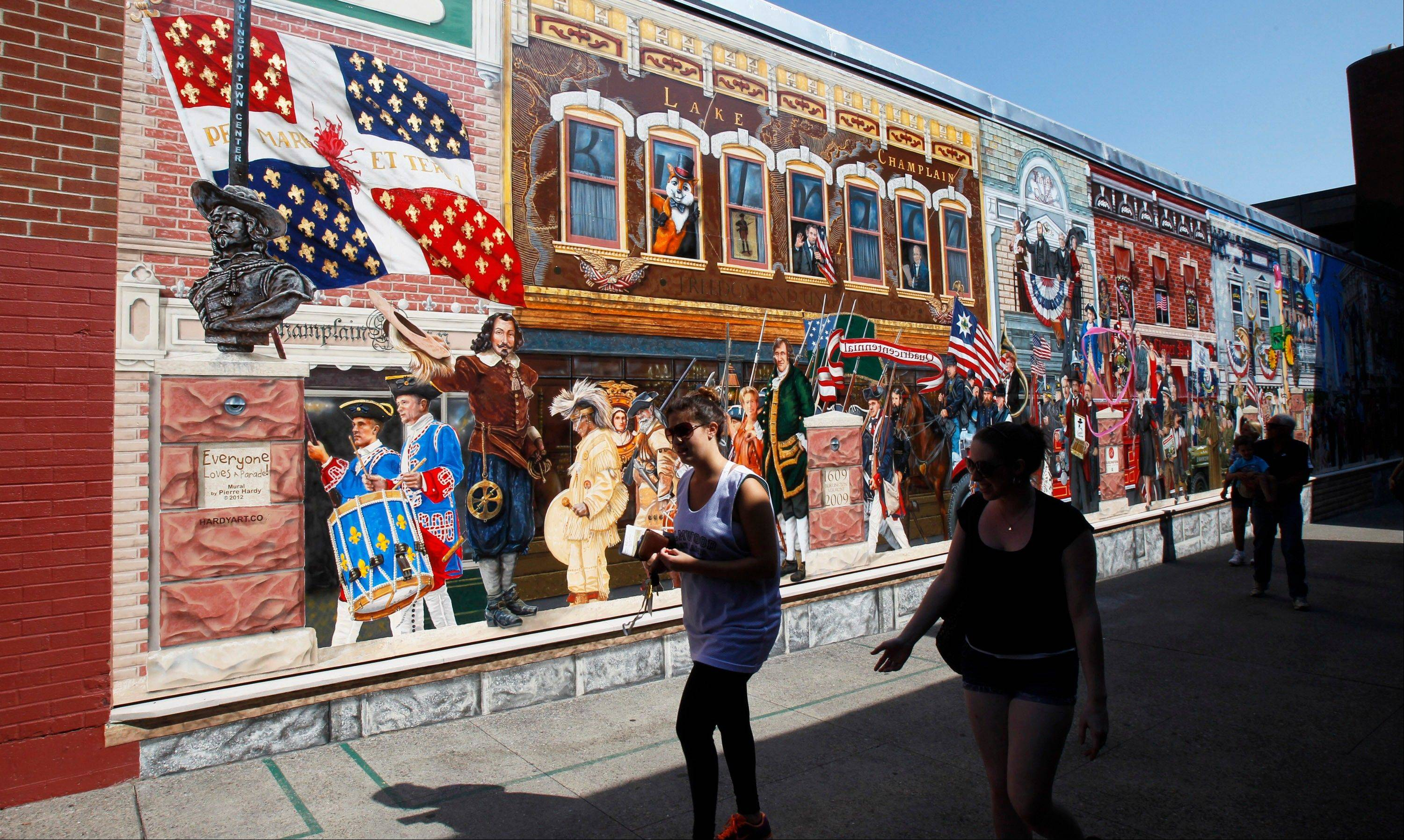 People walk past a mural wall at Church Street Marketplace in Burlington, Vt. Mountain and lake views along with fall foliage can be had for free in Vermont's largest city.