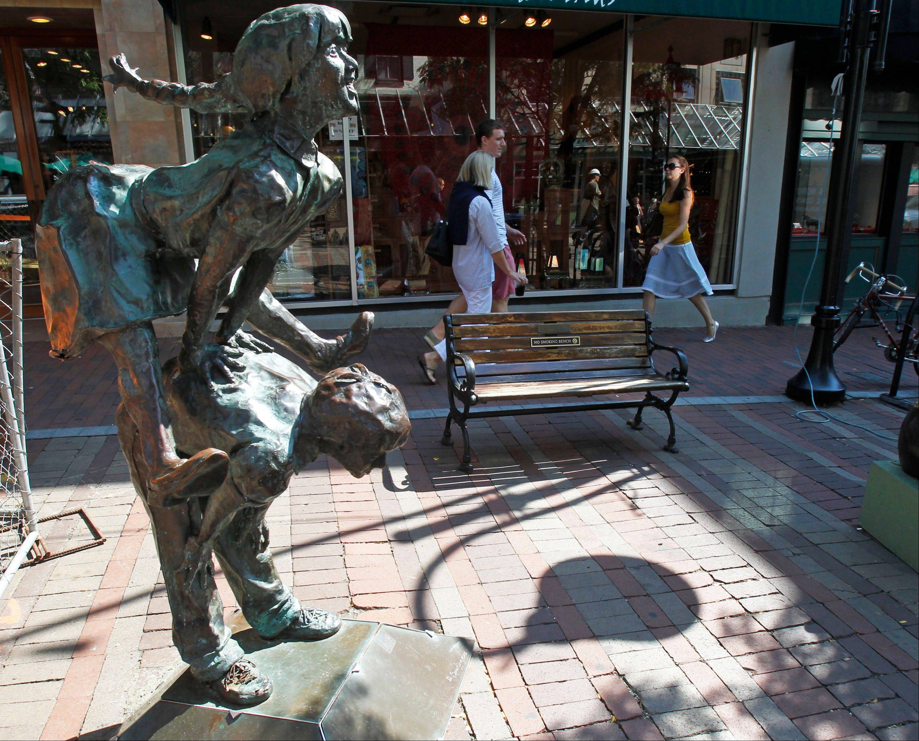 "People walk past a sculpture named ""Leapfroggers"" in the Church Street Marketplace in Burlington, Vt. Mountain and lake views along with fall foliage can be had for free in Vermont's largest city of Burlington."
