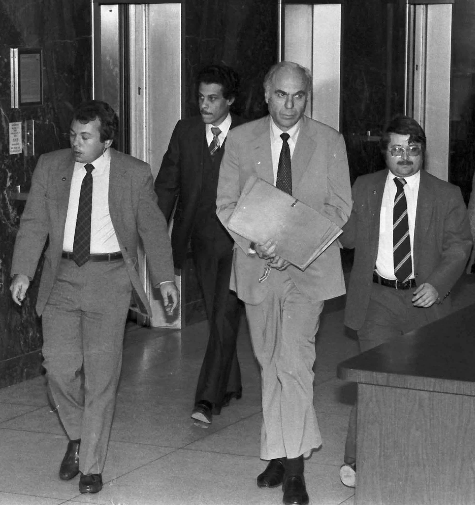 Ex-CIA agent Edwin Wilson, center, leaves federal court after a day of jury selection accompanied by U.S. Marshals in Houston. Wilson, a former CIA operative who was branded a traitor and convicted of shipping arms to Libya but whose conviction was later overturned after he served 22 years in prison, has died. He was 84.