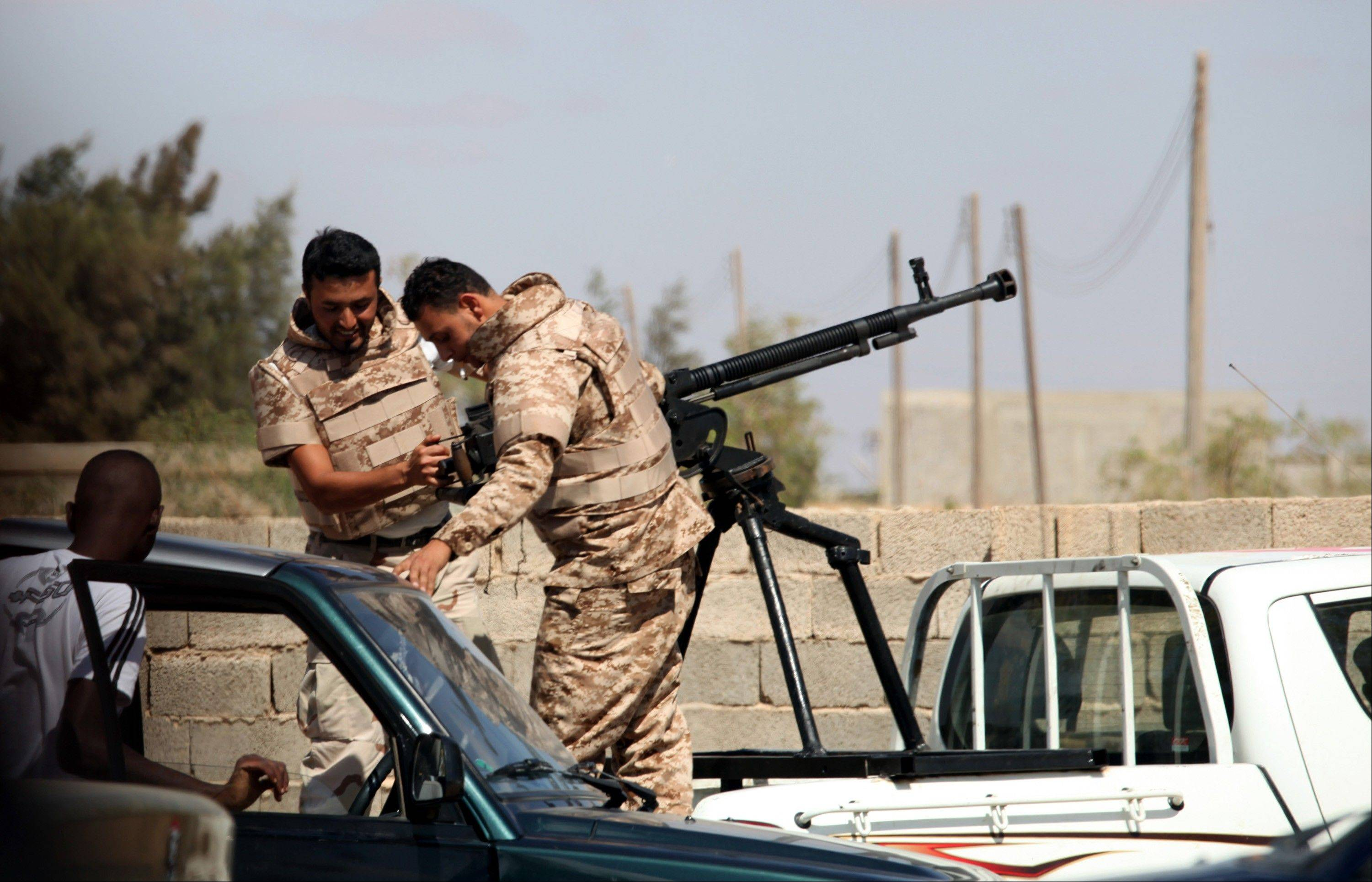 Soldiers from the Libyan National Army get ready Saturday to enter Rafallah al-sahati Islamic Militia Brigades compound, one of the compound buildings can be seen behind the wall, in Benghazi, Libya.