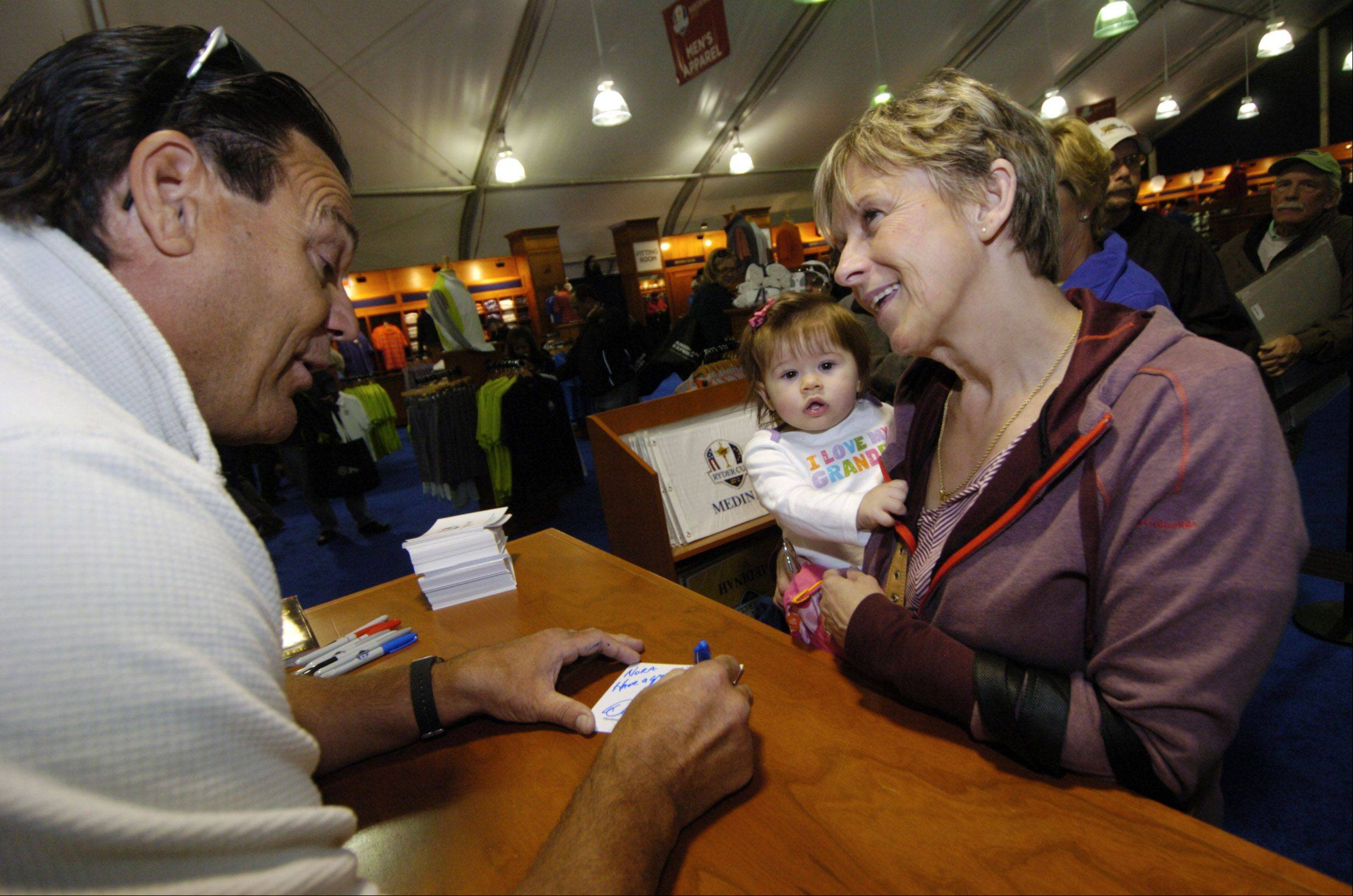 Former Chicago Bears Hall of Fame defensive lineman Dan Hampton signs an autograph for Barbara Divita and her granddaughter Nora Spiewak, 1, both of Roselle, during the Ryder Cup pre-sale Saturday at Medinah Country Club.