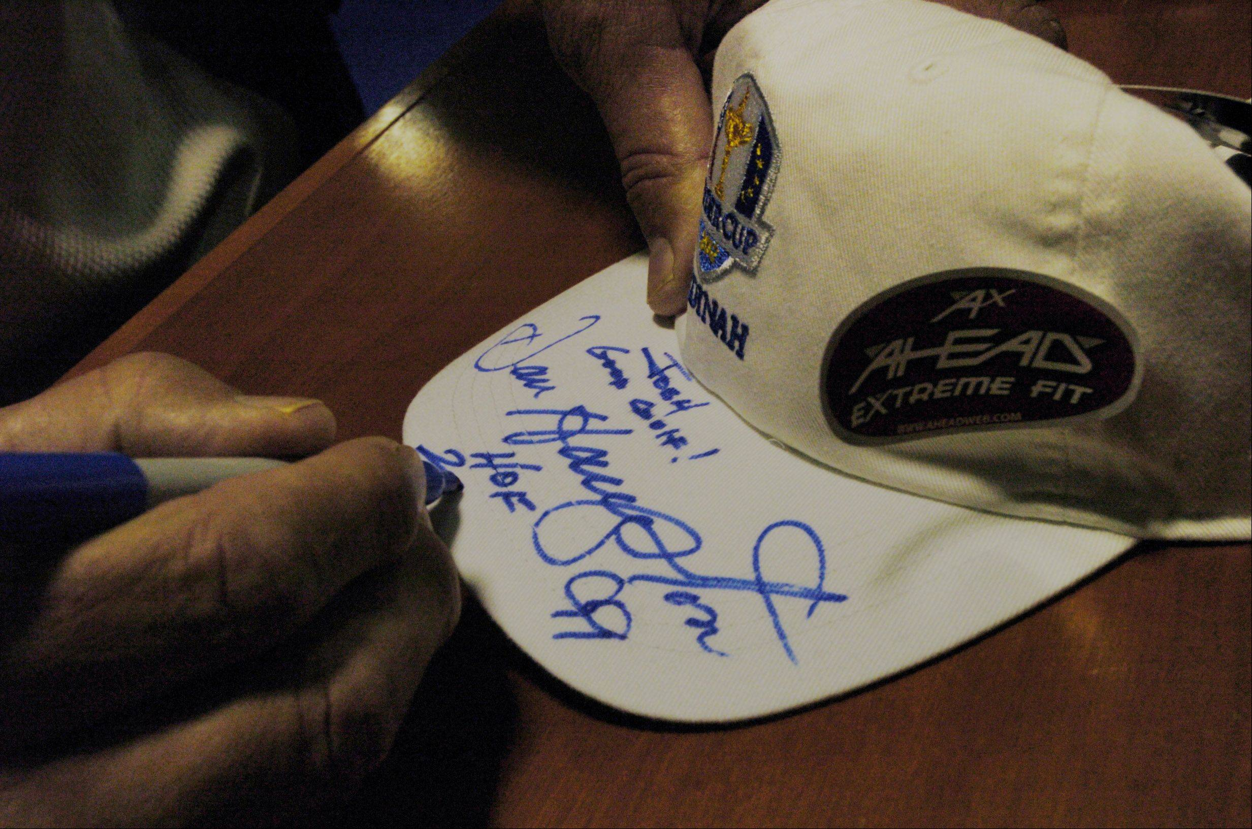 Dan Hampton, Former Chicago Bears Hall of Fame defensive lineman, autographs a Ryder Cup hat Saturday during the Ryder Cup pre-sale at Medinah Country Club.