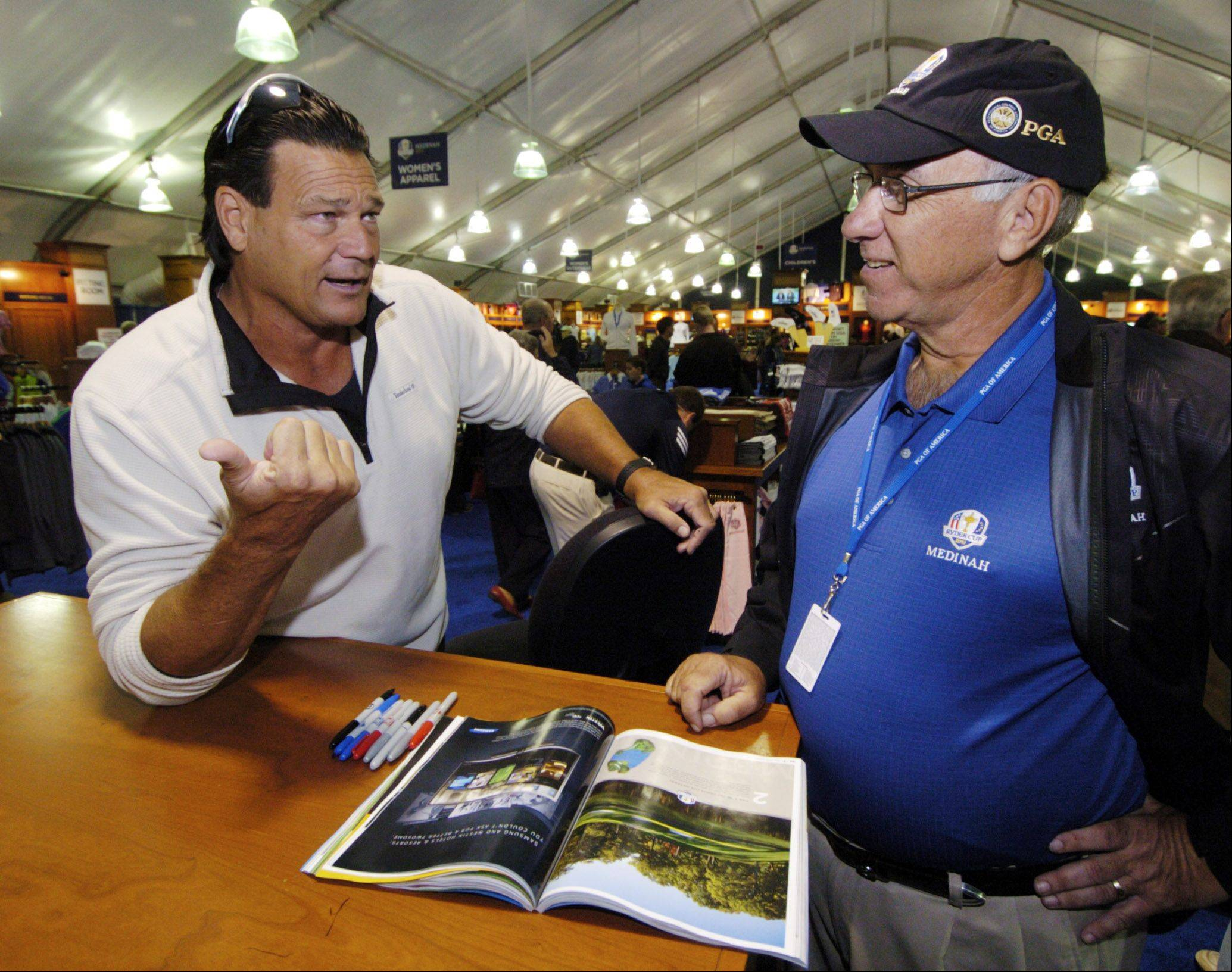 Former Chicago Bears Hall of Fame defensive lineman Dan Hampton talks about golf with club member Jim Grosskopf of Naperville while signing autographs Saturday during the Ryder Cup pre-sale at Medinah Country Club.