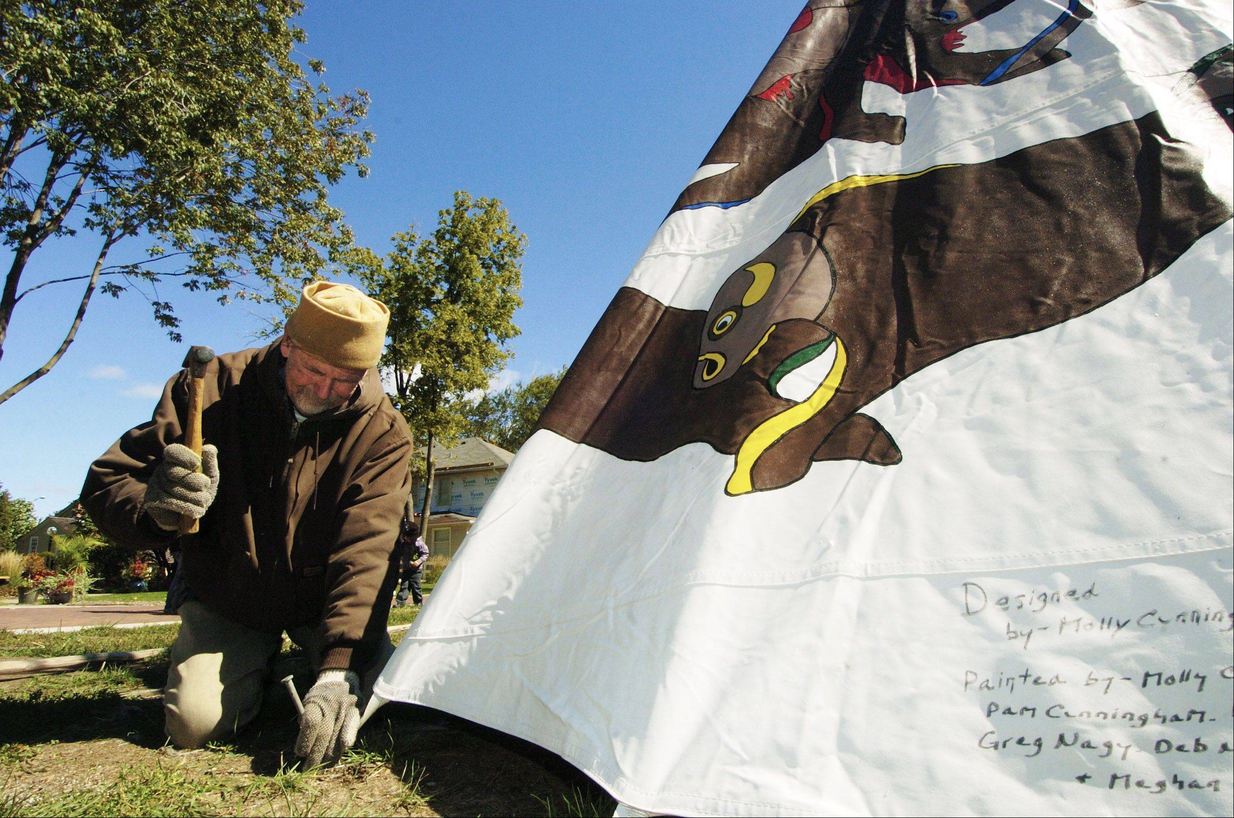 Gregg Walkstall of Chicago hammers stakes for a teepee during Saturday's annual Harvest Pow Wow at the Naper Settlement in Naperville.