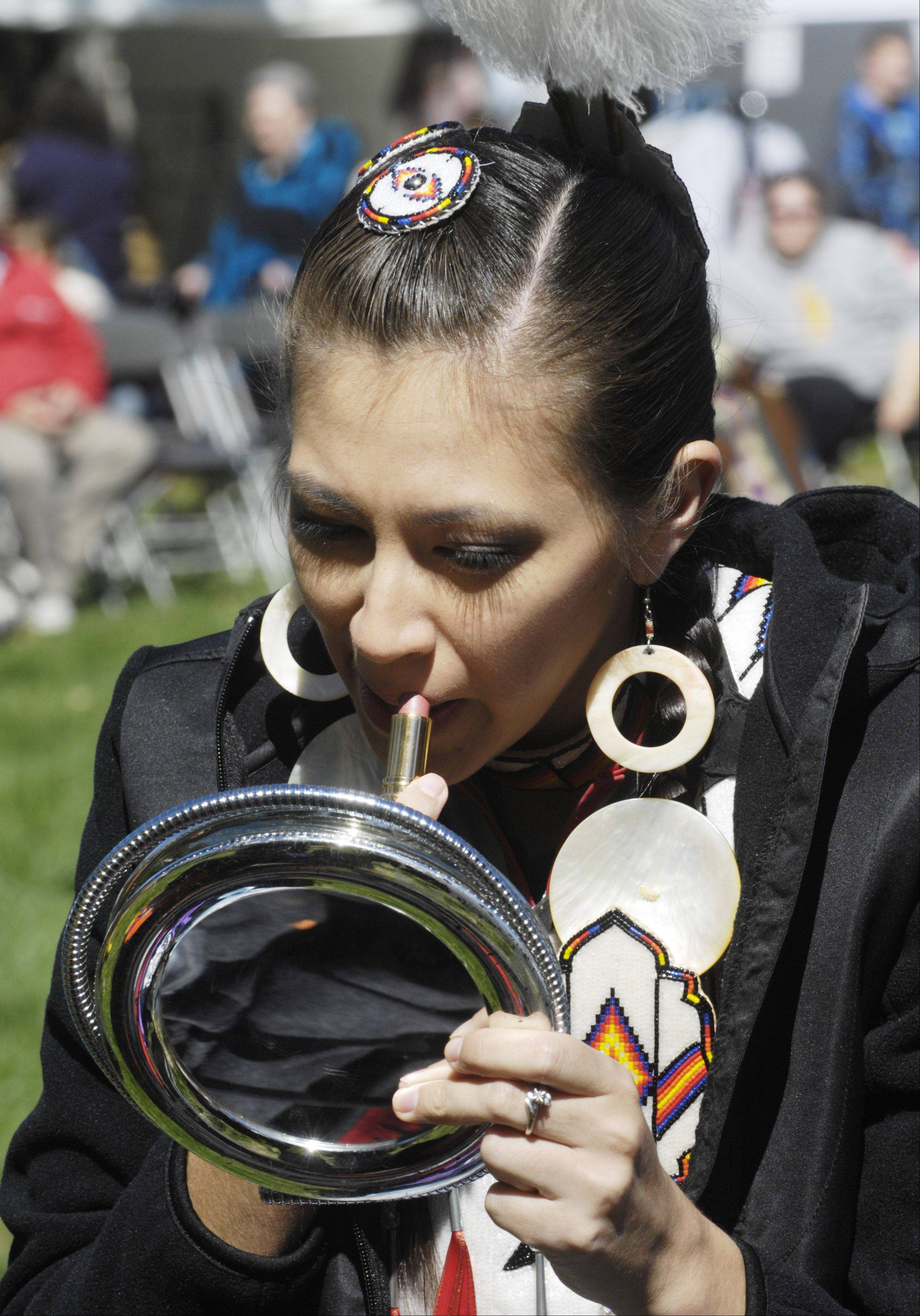Nicole Sine, a member of the Ho-Chunk tribe who lives in Stillwater, Oklahoma, applies lipstick prior to the grand entrance at Saturday's annual Midwest SOARRING Foundation Harvest Pow Wow at the Naper Settlement in Naperville.