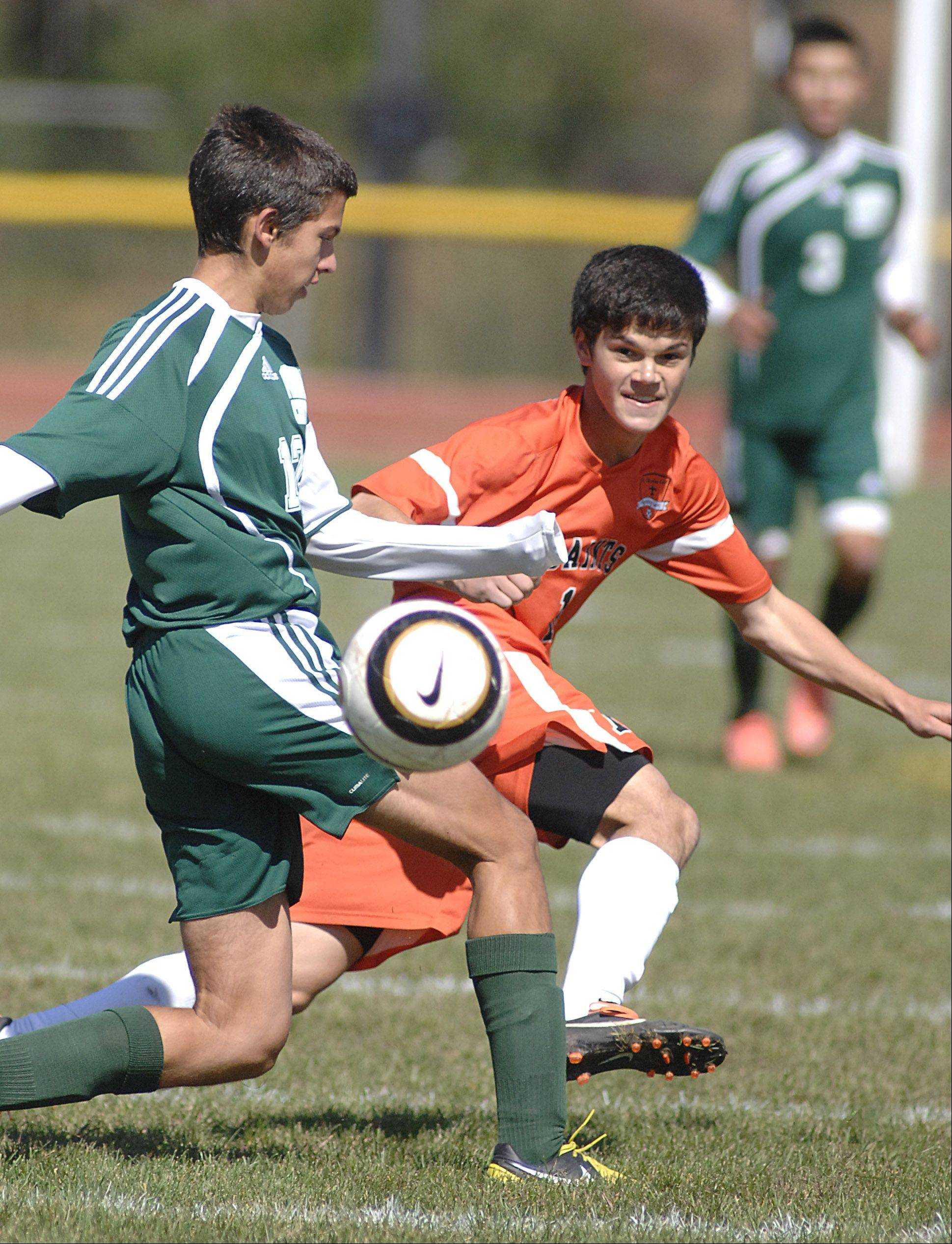 St. Charles East's Kevin Kurtz kicks the ball past an attempted leg block by Plainfield Central's Mike Giocolo in the first half on Saturday, September 22.