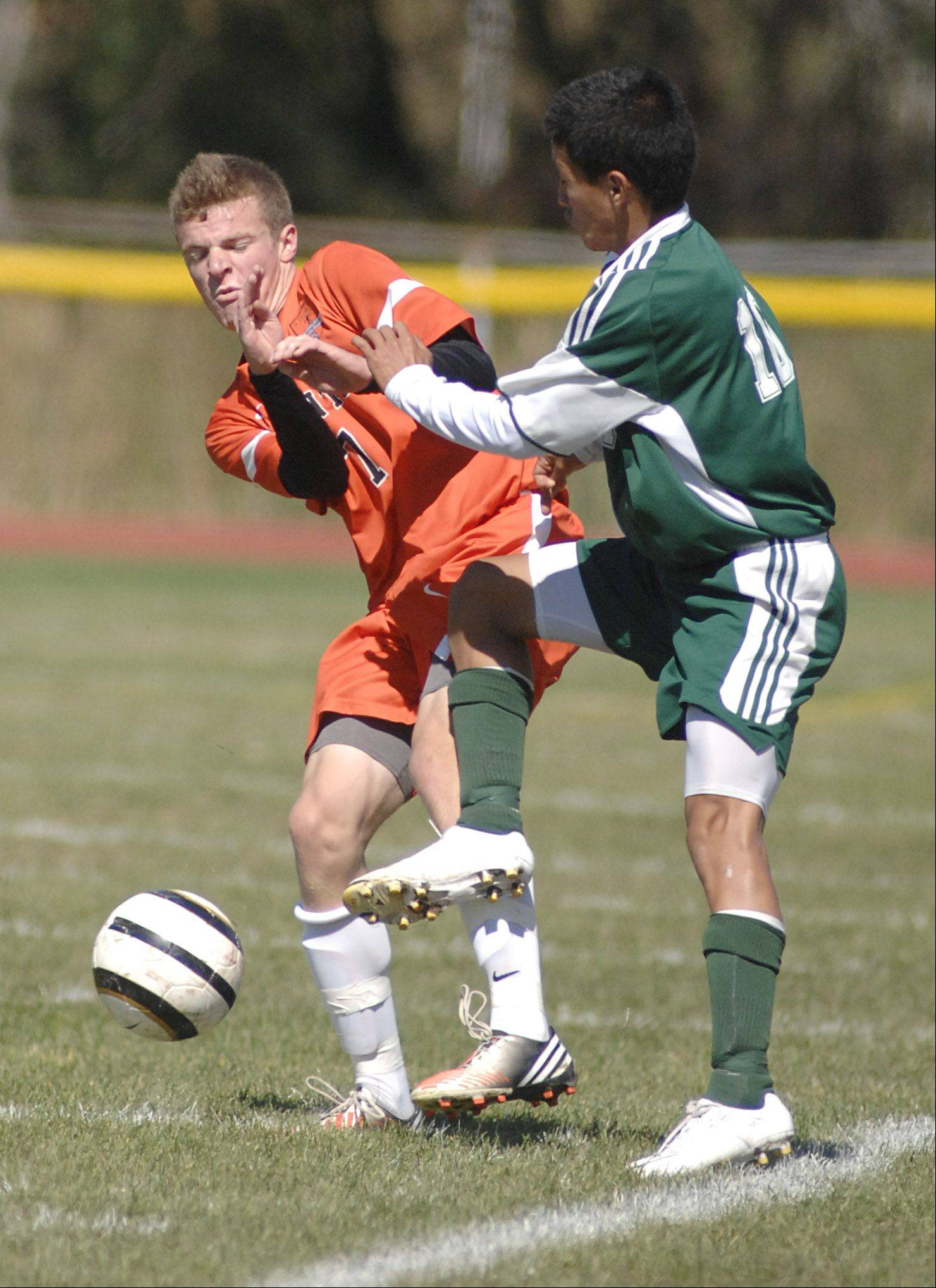 St. Charles East's Jacob Sterling winces as Plainfield Central's Miguel Duran kicks the ball at close range in the first half on Saturday, September 22.