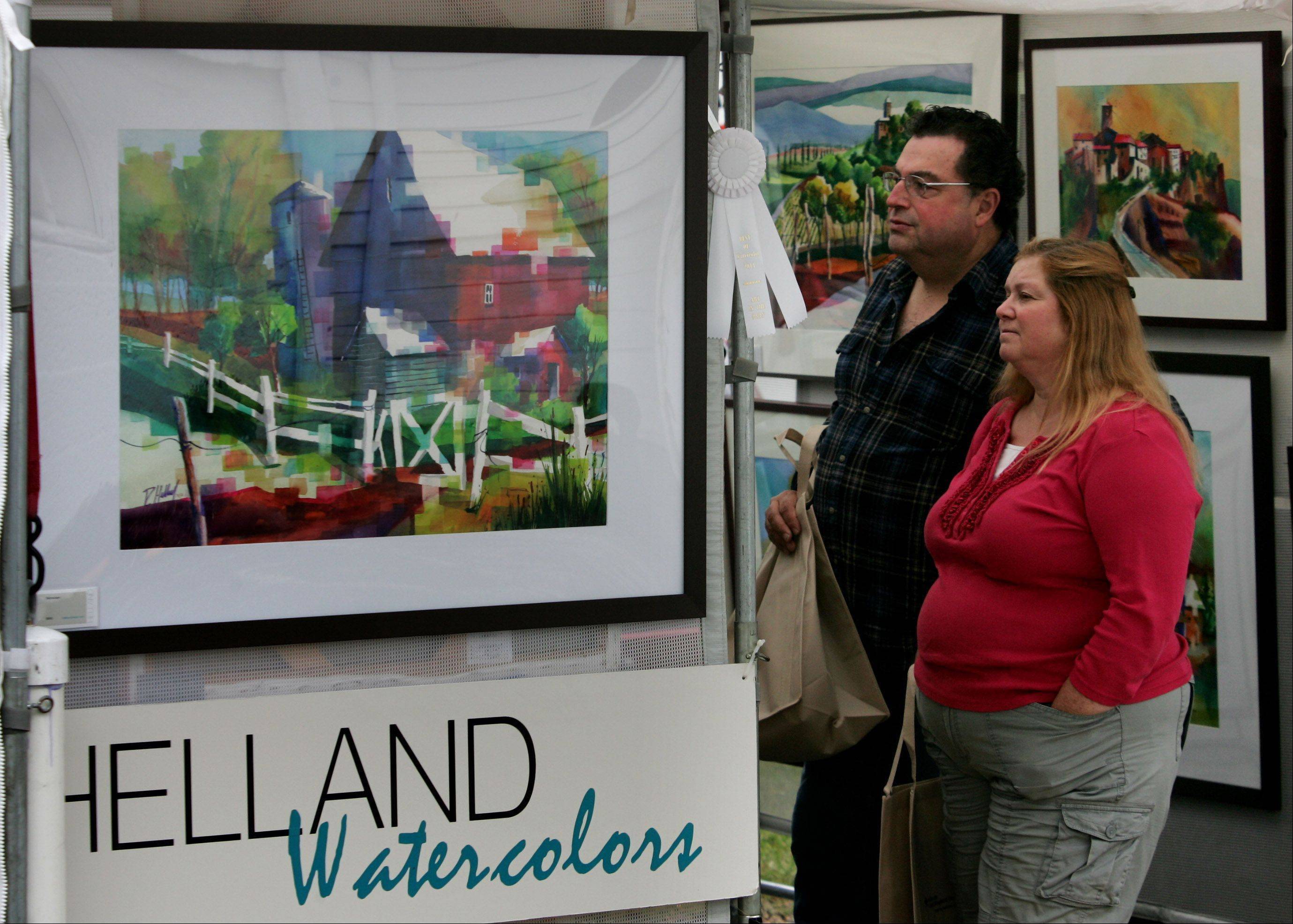 Andre and Gail Peters of Cary look at the artwork of Richard Helland of Palatine during the 2011 Art in the Barn. This painting won first place for watercolors in the juried show.