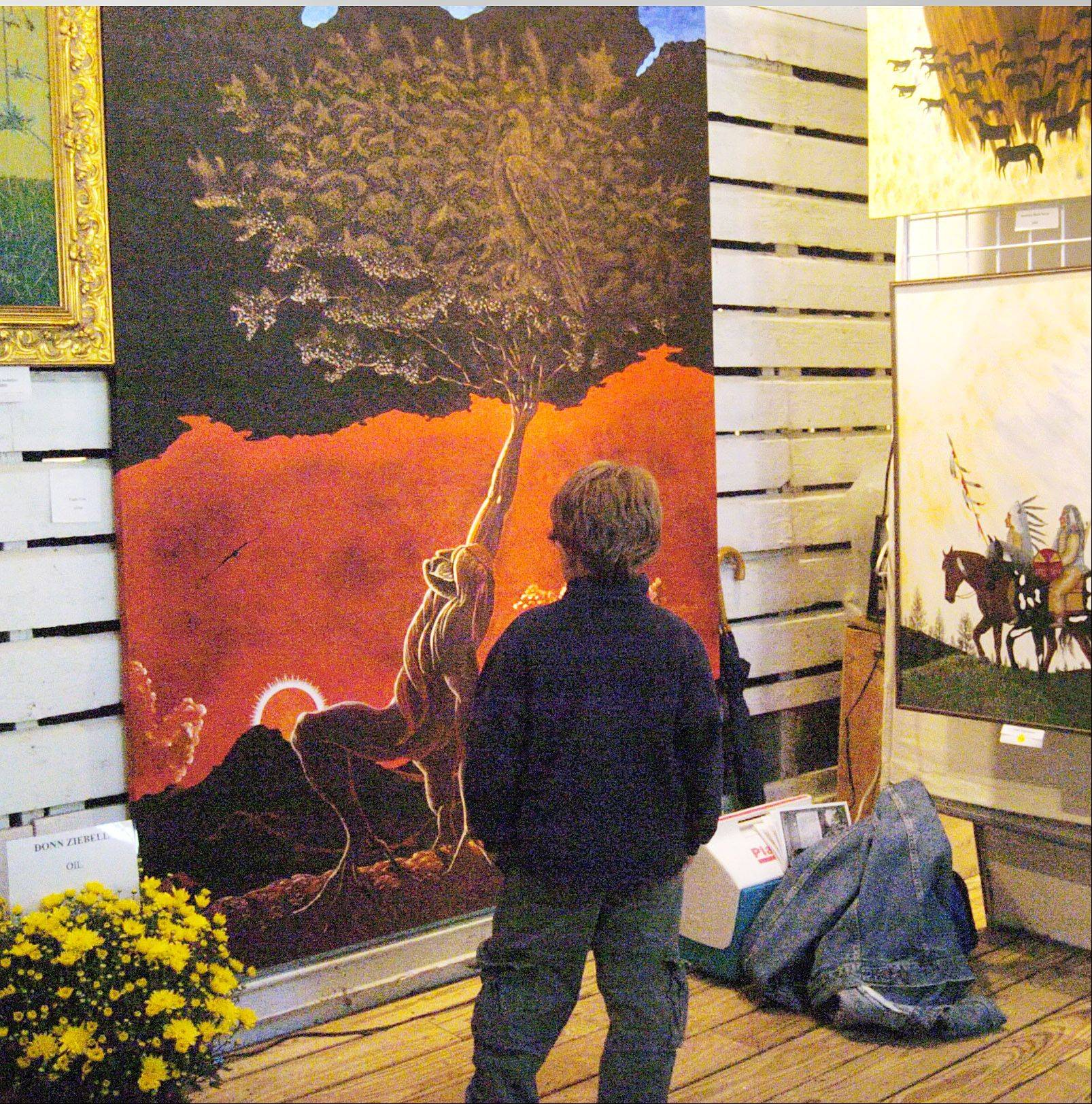 A boy is enchanted by a painting features at a previous Art in the Barn.