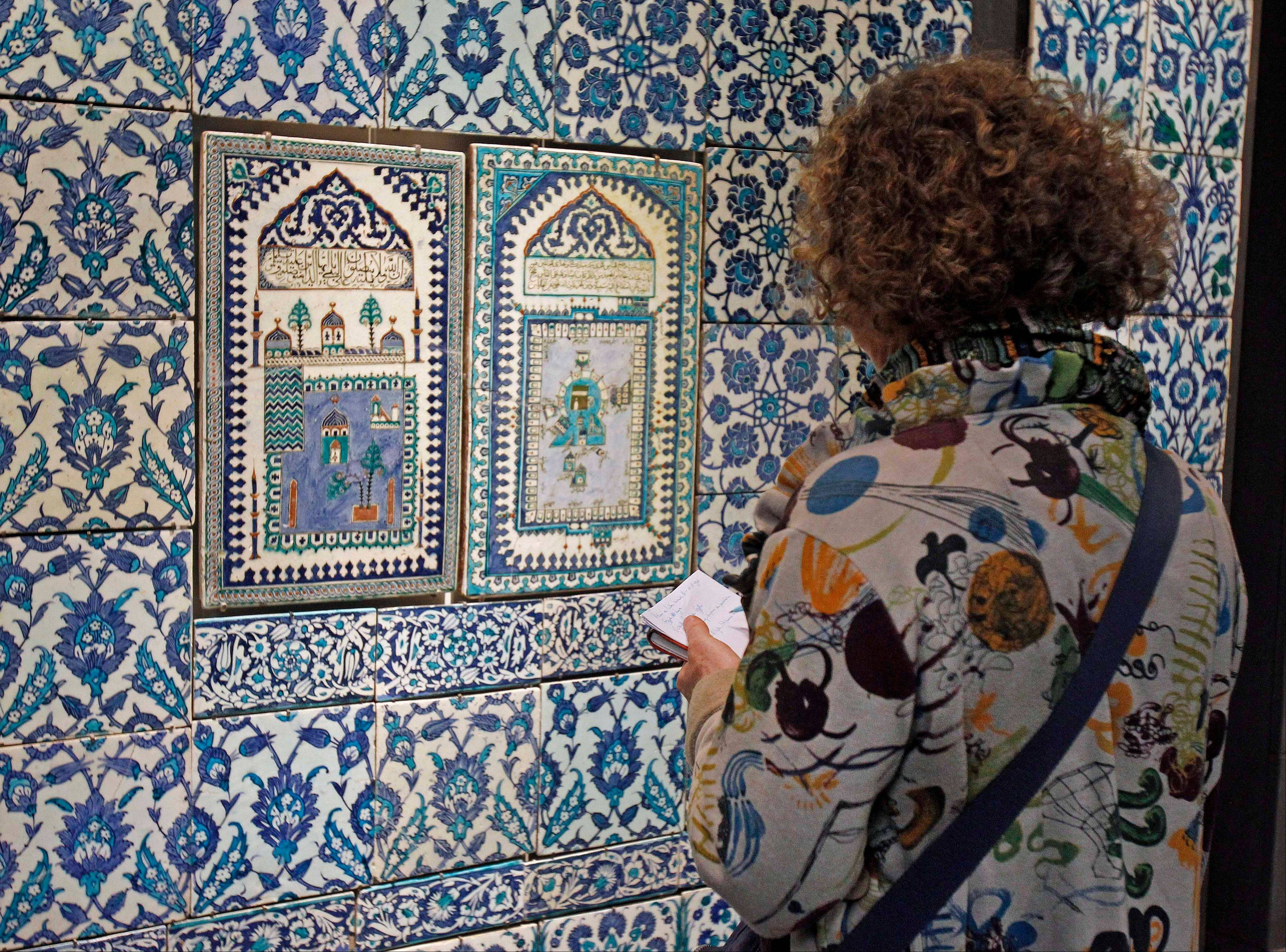 A member of the media examines a ceramic tile wall displayed at the Louvre museum in Paris. The Louvre museum is unveiling its new wing and galleries dedicated to the arts of Islam, and new dragonfly shaped building marking the museum�s greatest development since the iconic glass pyramid constructed 20 years ago.