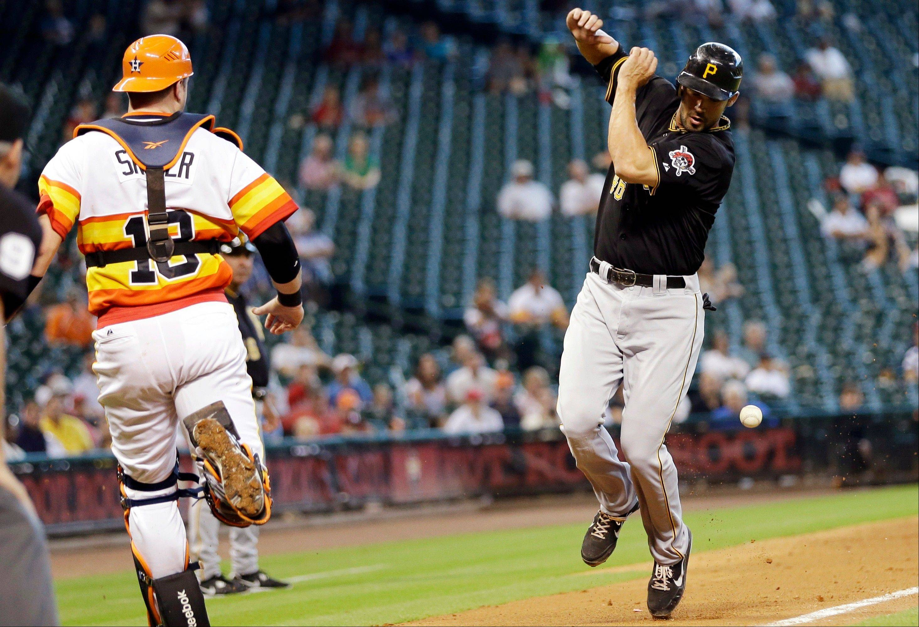 Pittsburgh�s Garrett Jones avoids being hit by a foul ball hit by pitcher A.J. Burnett as Astros catcher Chris Snyder runs down the third base line during the fourth inning Sunday in Houston.